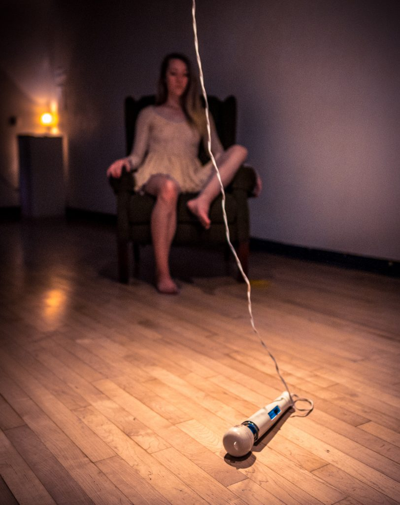Photo of a vibrator on the gallery floor with a slightly out of focus Cortnee Brush in a chair in the background