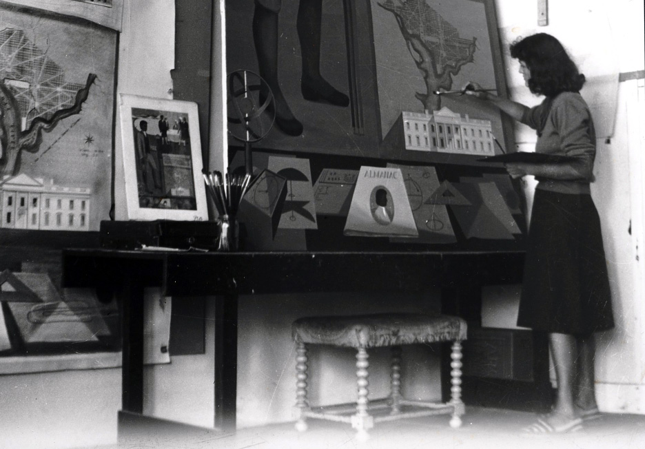 black-and-white photograph of Maxine Merlino working on a painting