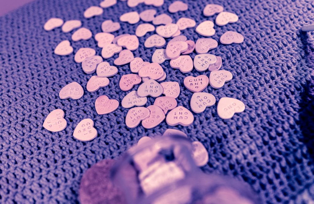"dozens of small ceramic candy hearts made by Claudia Solorzano on a crocheted table top including many repetitions of  ""Cum On!"" and ""Suck it up"""