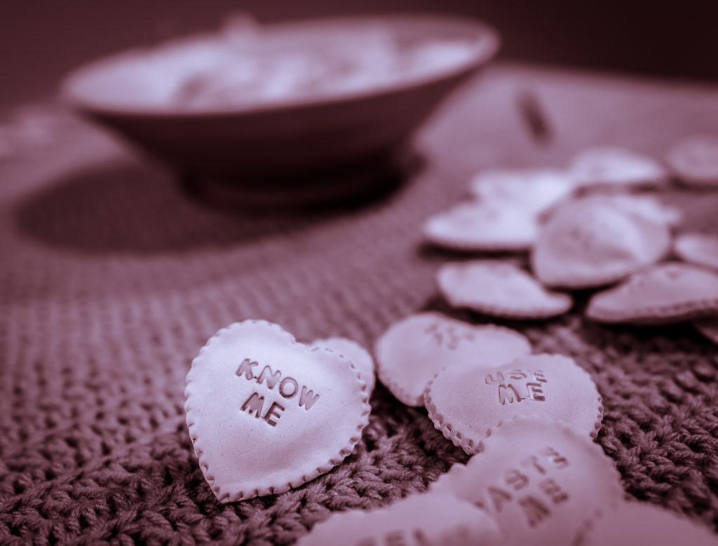 "Claudia Solorzano's Ceramic-ravioli-candy-heart with the words ""Know Me"" on it."