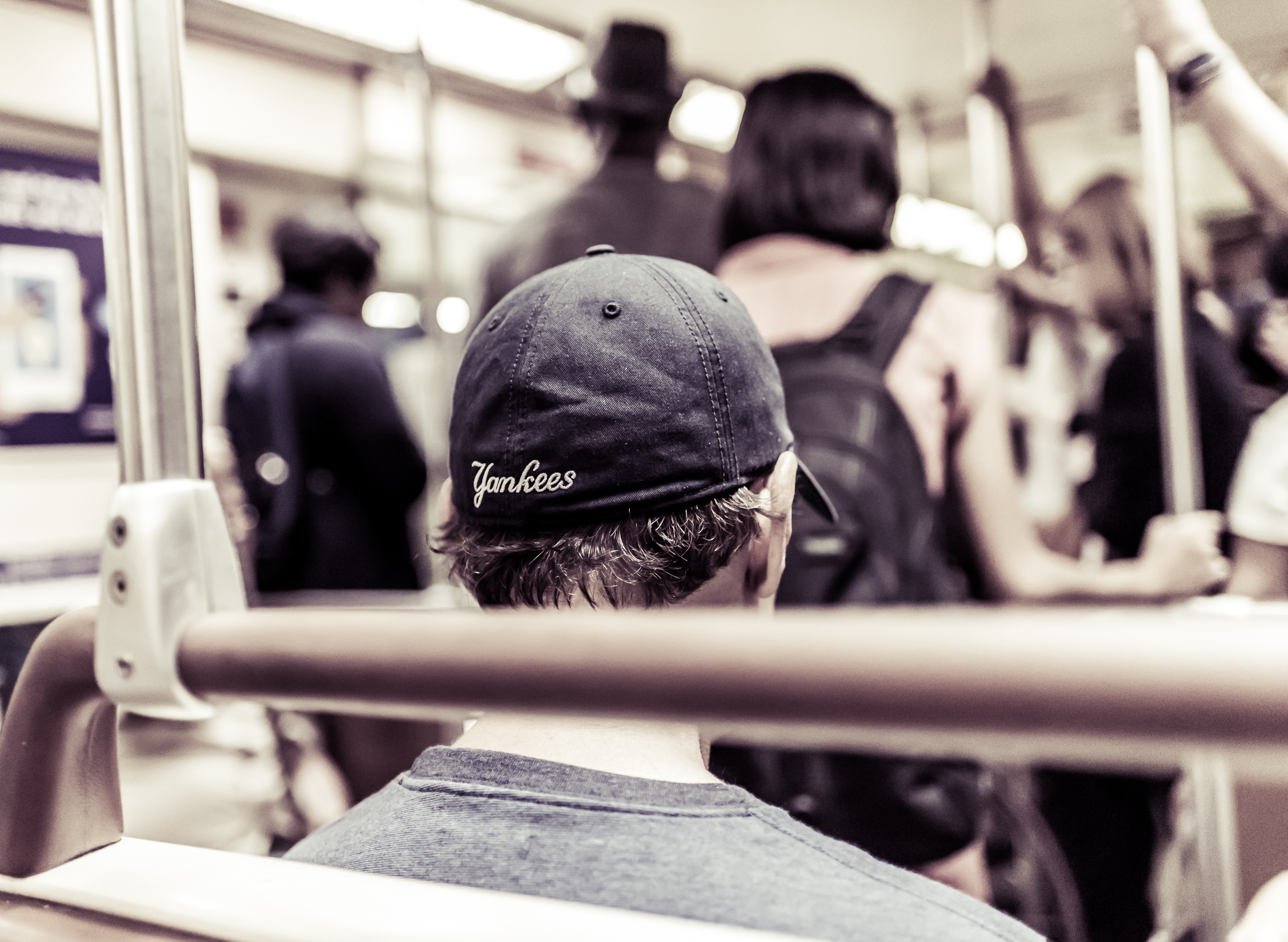 "The back of a subway rider's cap featuring the word ""Yankees"""