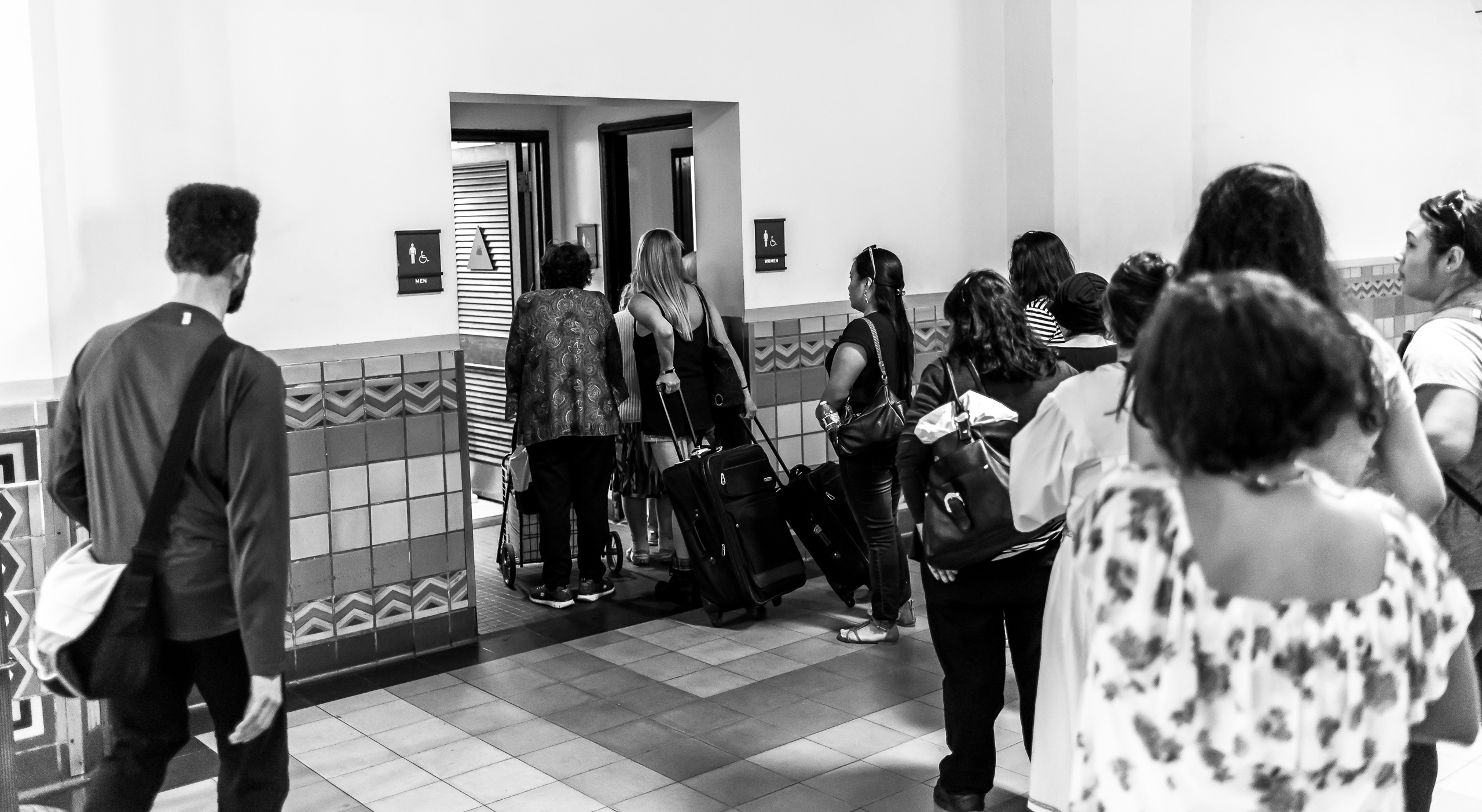Bathrooms at Union Station in Los Angeles, California. One man walks into an empty men's room as a long line of women wait outside the women's room