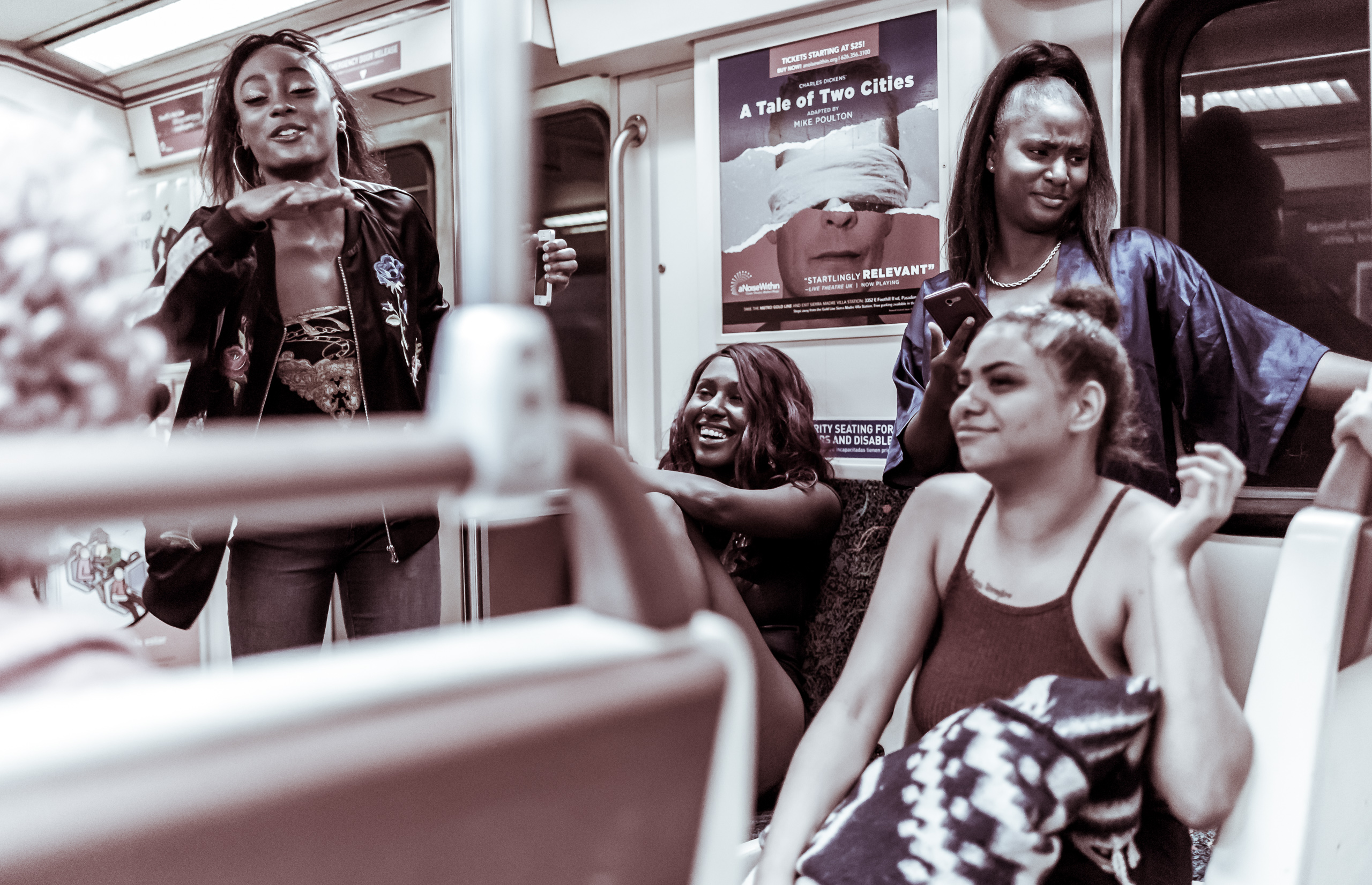 A group of 6 women singing together as the Red Line heads from Hollywood back toward Union Station.