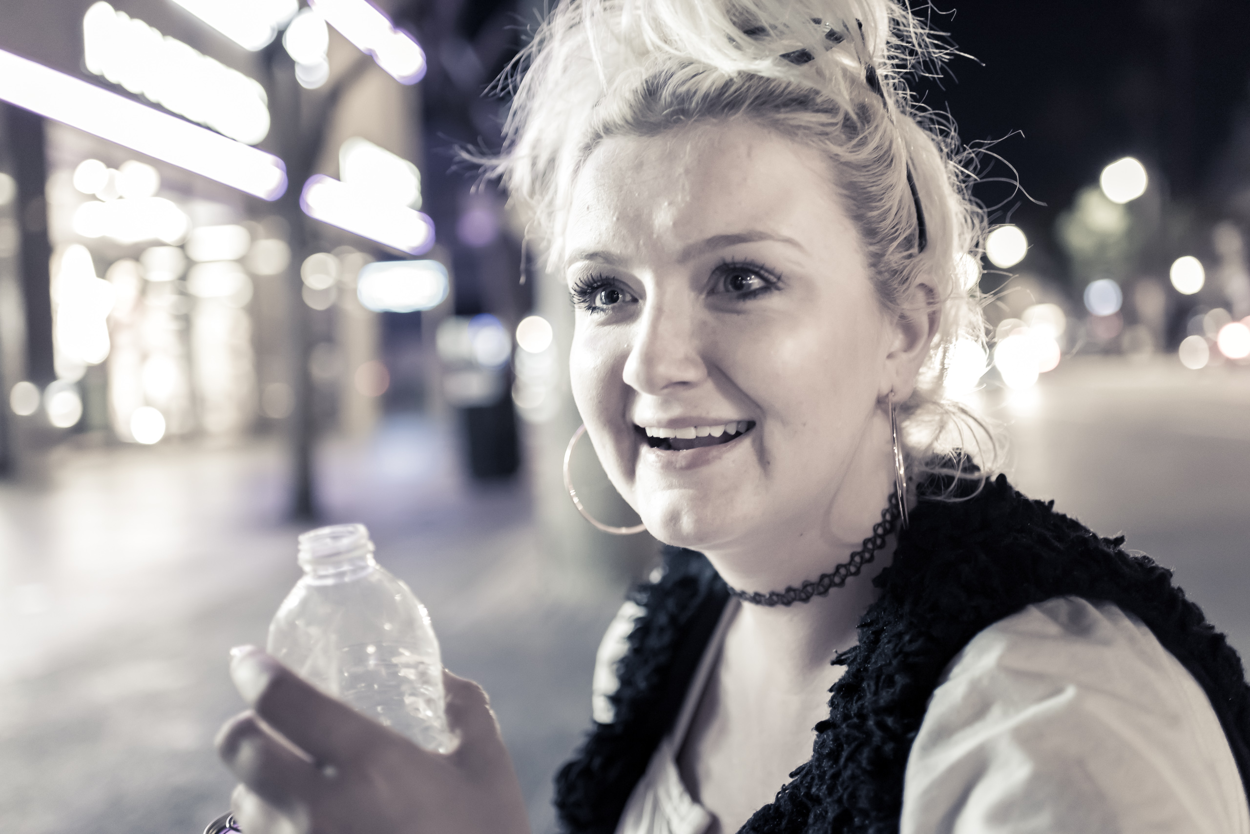 Kristina, sitting on the curb on Hollywood Blvd between Vine & Highland. She drinks a bottle of water, smokes a cigarette, and looks out, smiling and thinking