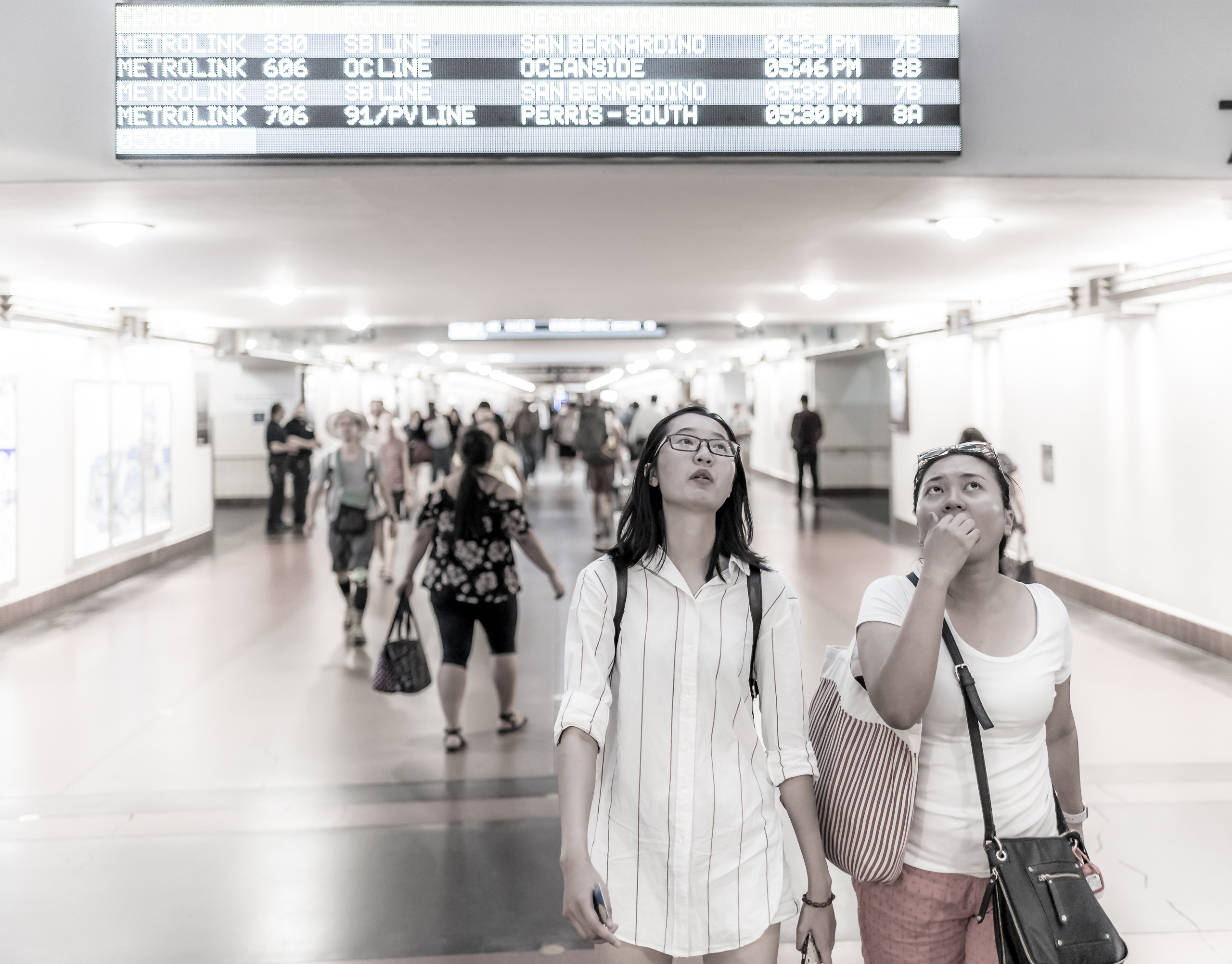 Two people walking through the main corridor at Union Station in Downtown Los Angeles and looking up at a schedule board