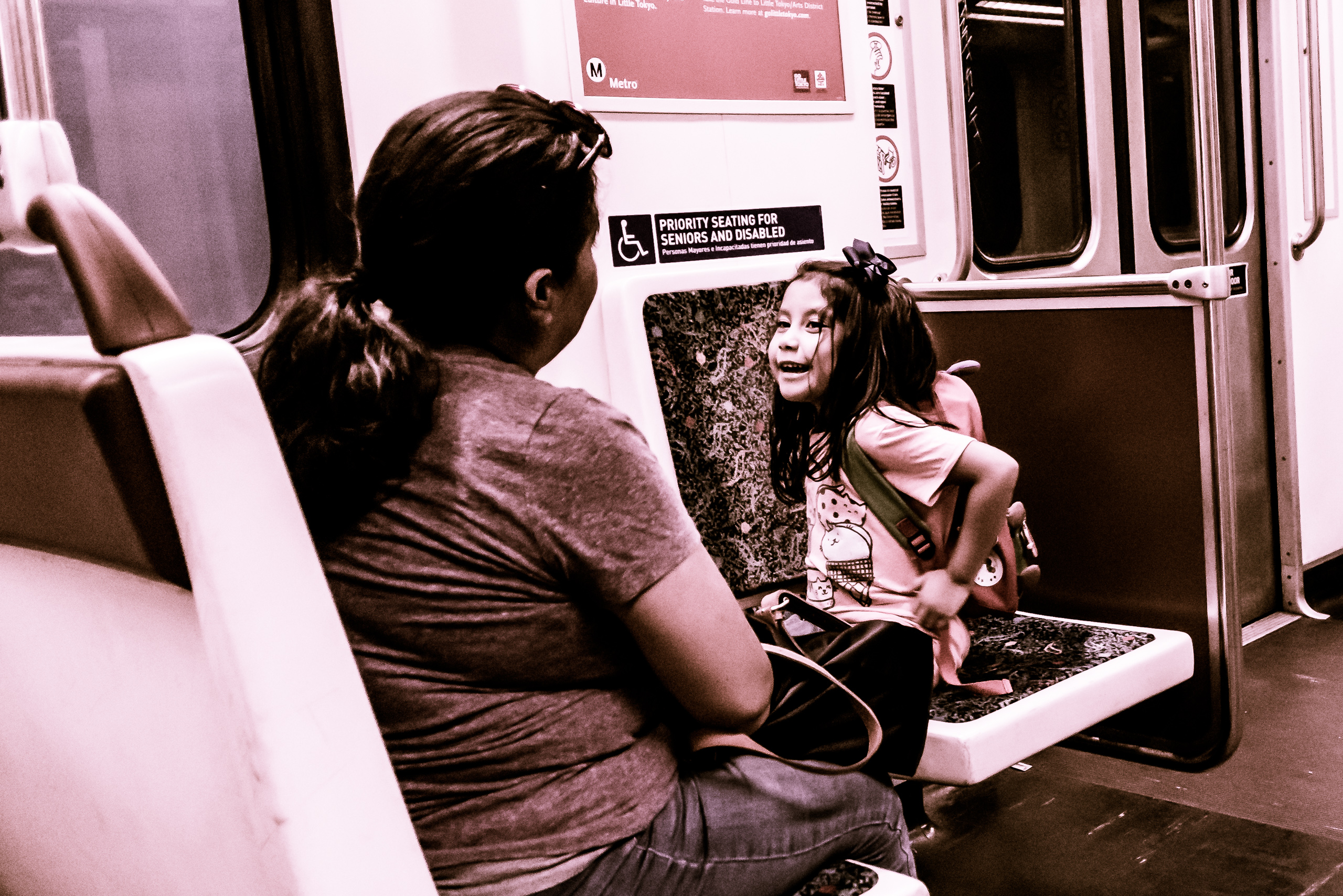 A young girl on the subway, smiling and talking intensely to an older adult.
