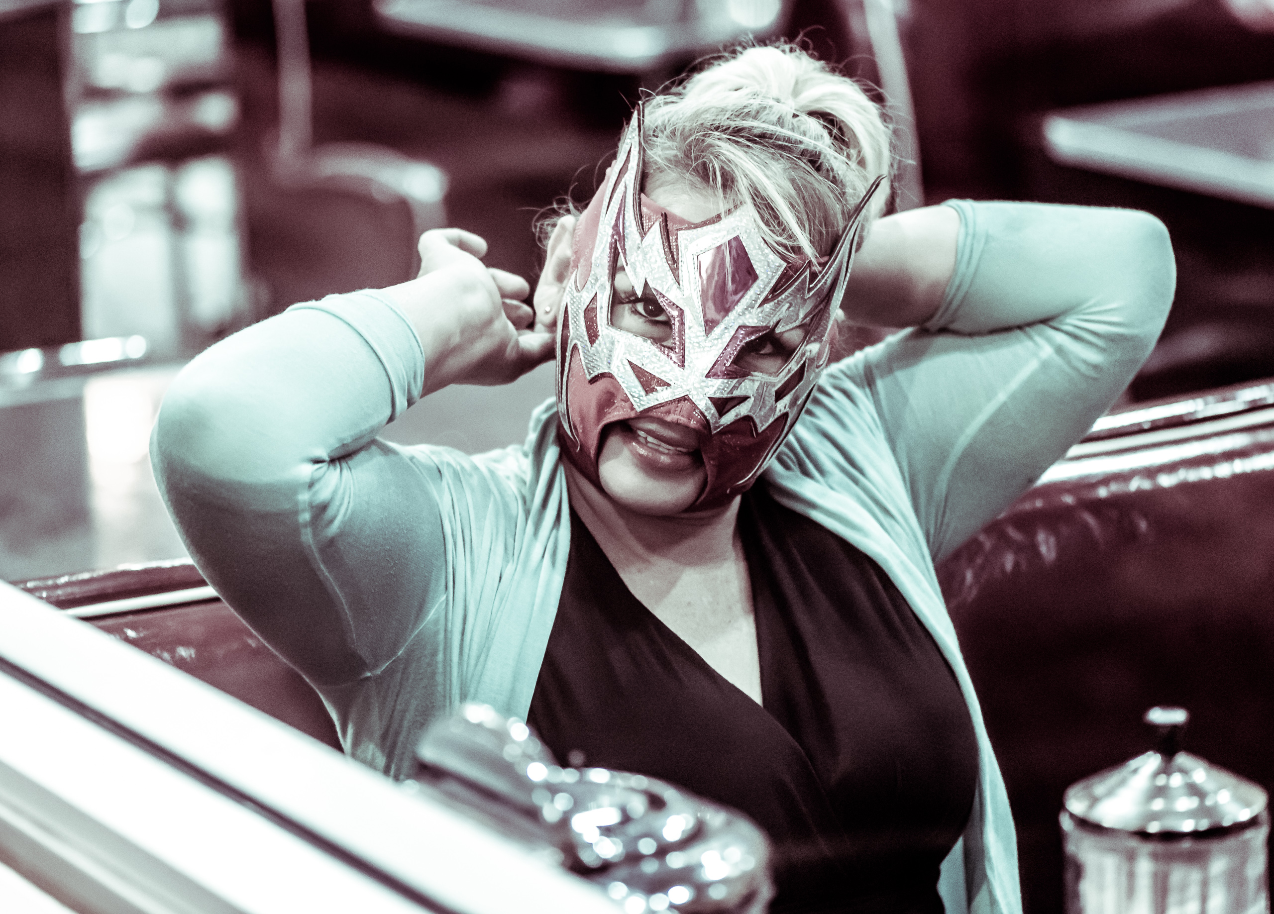 a woman sitting in a booth at Johnny Rockets at Hollywood & Highland in Los Angeles, CA trying on a Lucha Libre mask