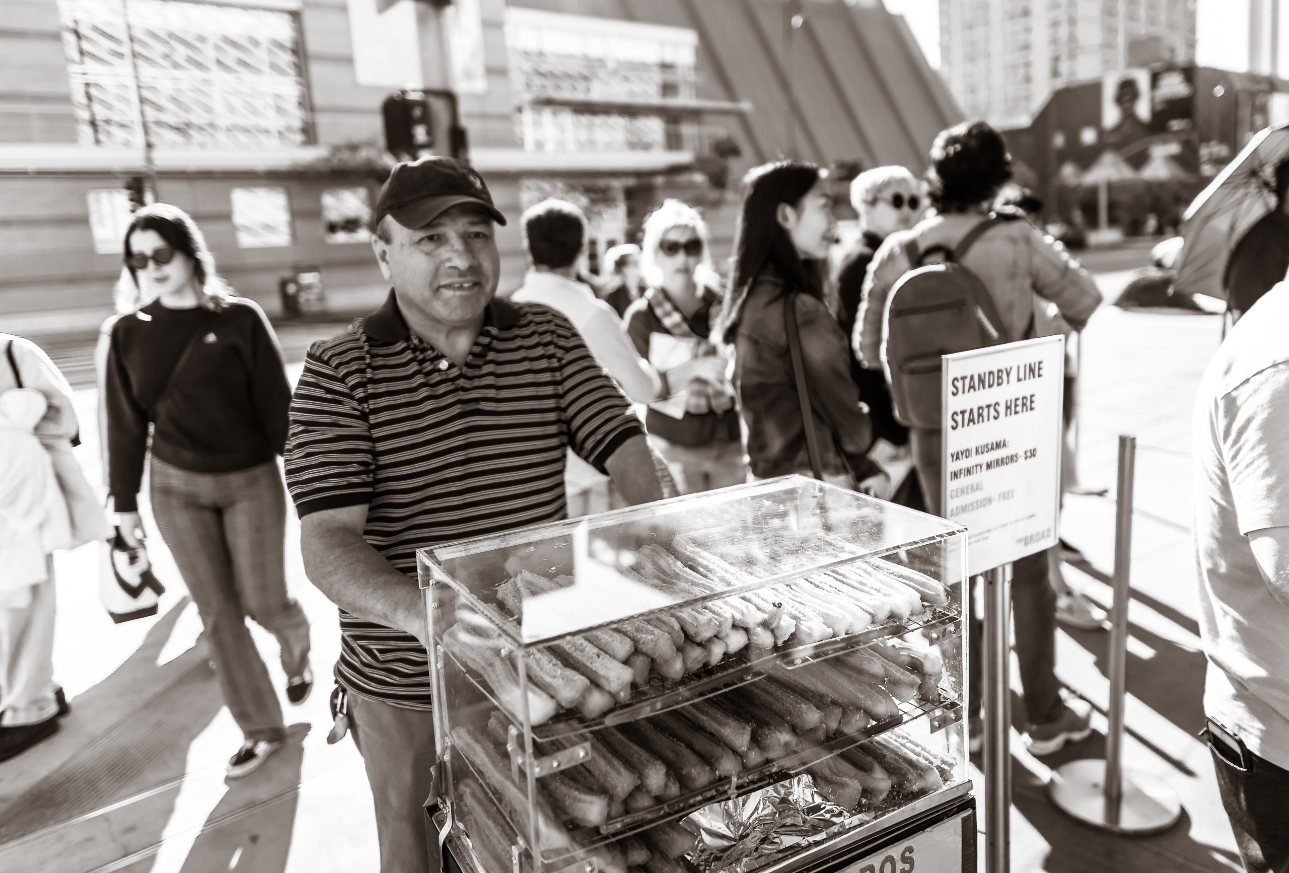 A street vendor on Grand Avenue sells fresh churros to the crowd waiting in the long standby line at the Yayoi Kusama exhibition at The Broad Museum in Downtown Los Angeles