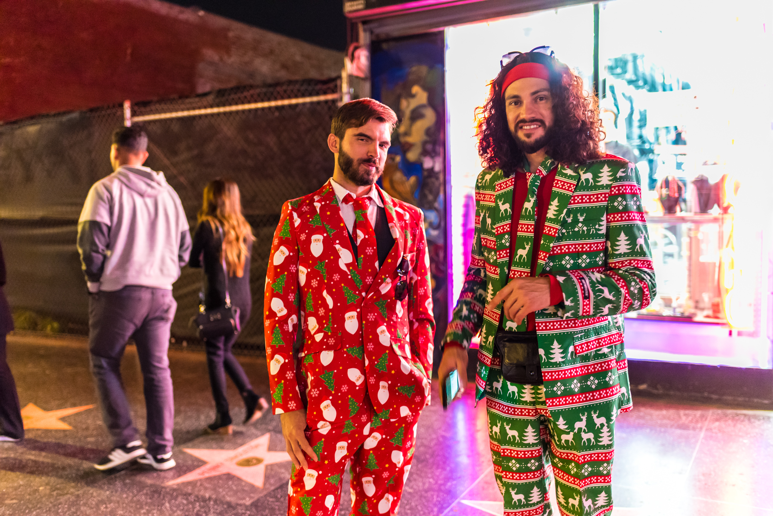 Two guys in Christmas suits on Hollywood Blvd. One in a red suit and one in a green suit. Both suits are decorated with Christmas motifs like trees, reindeer, etc