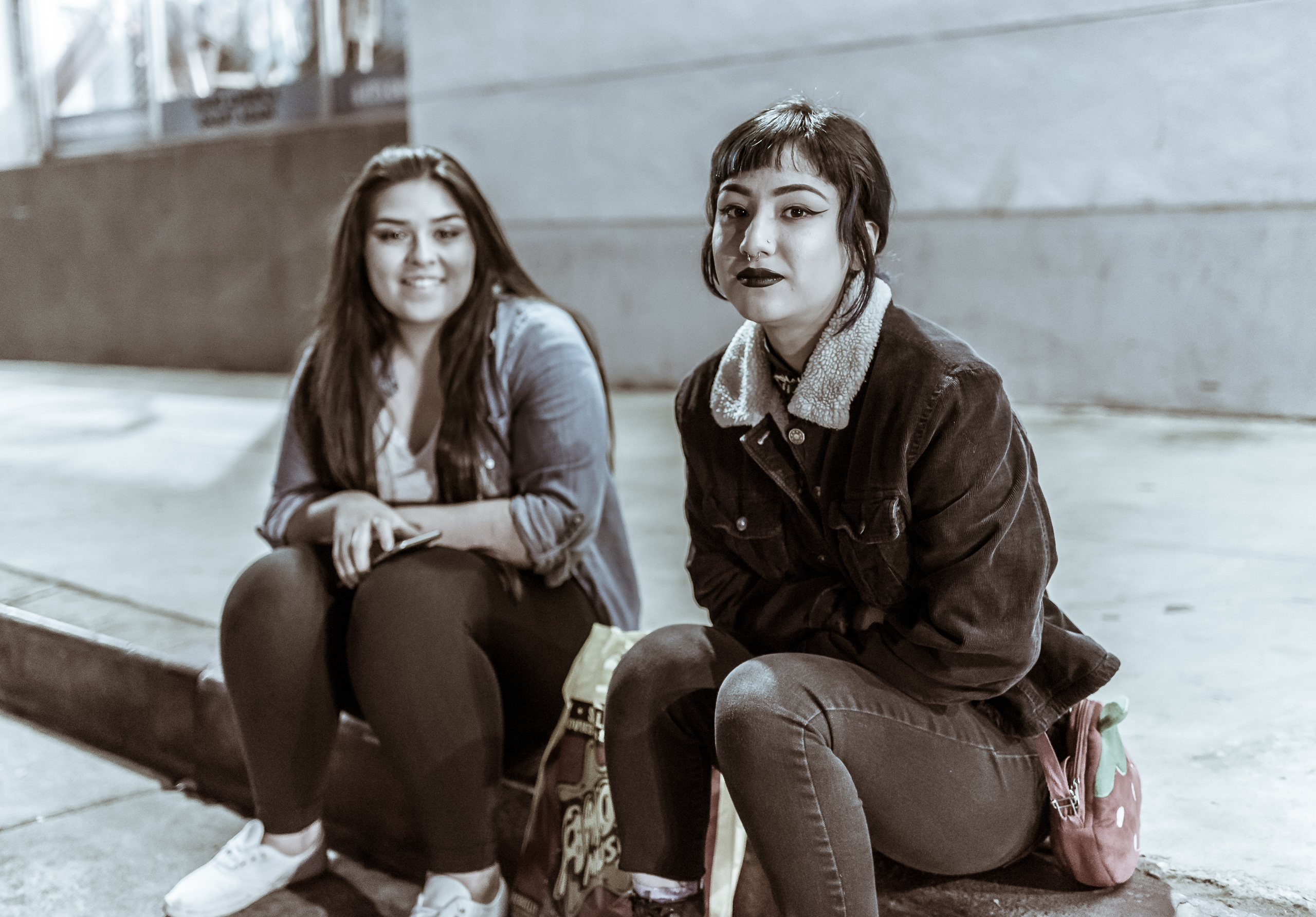 two women sitting on the curb on Ivar Avenue outside Amoeba Music in Hollywood, Los Angeles, California