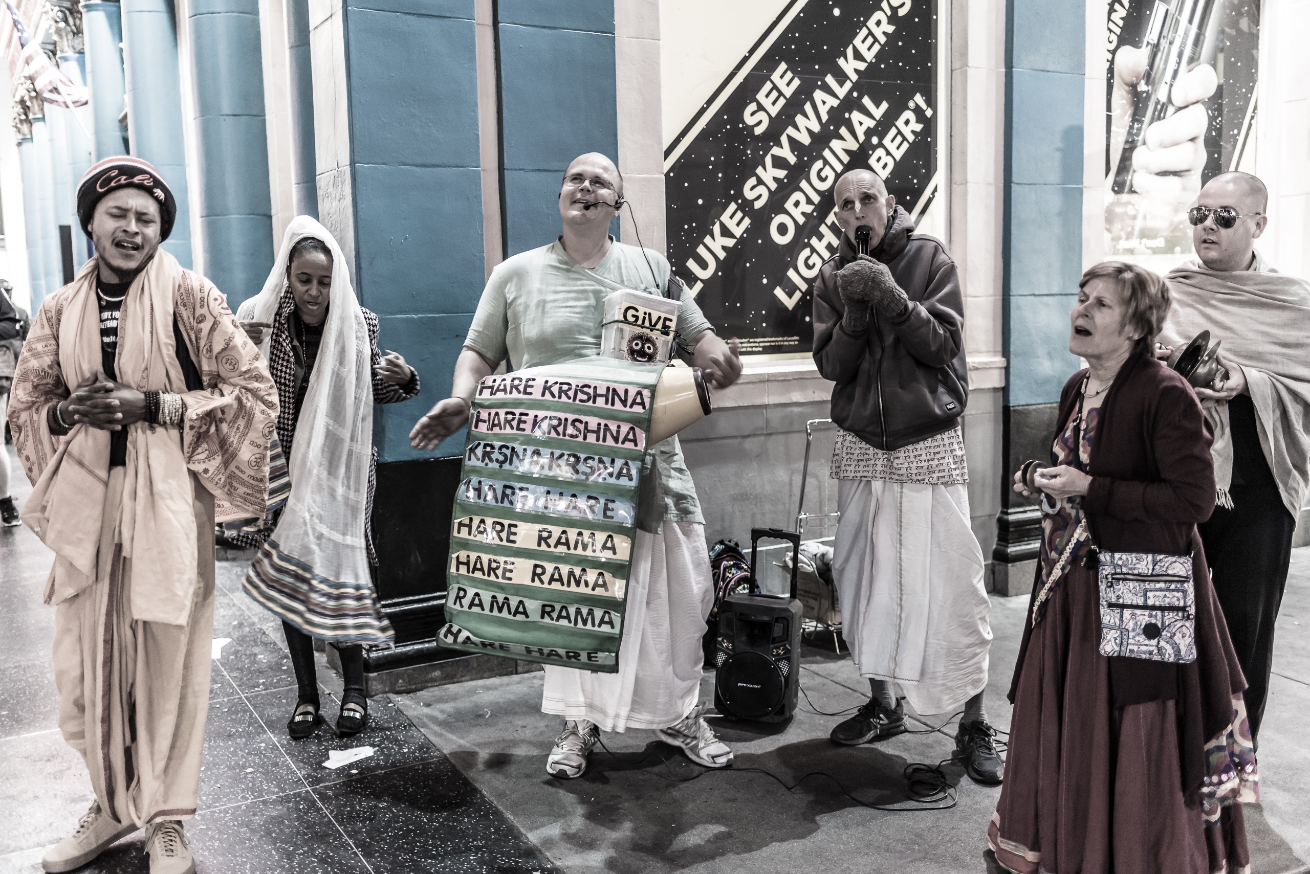 """a group of """"Hare Krishna's"""" chanting on a street corner on Hollywood Blvd in front of a sign about Luke Skywalker's Lightsaber"""