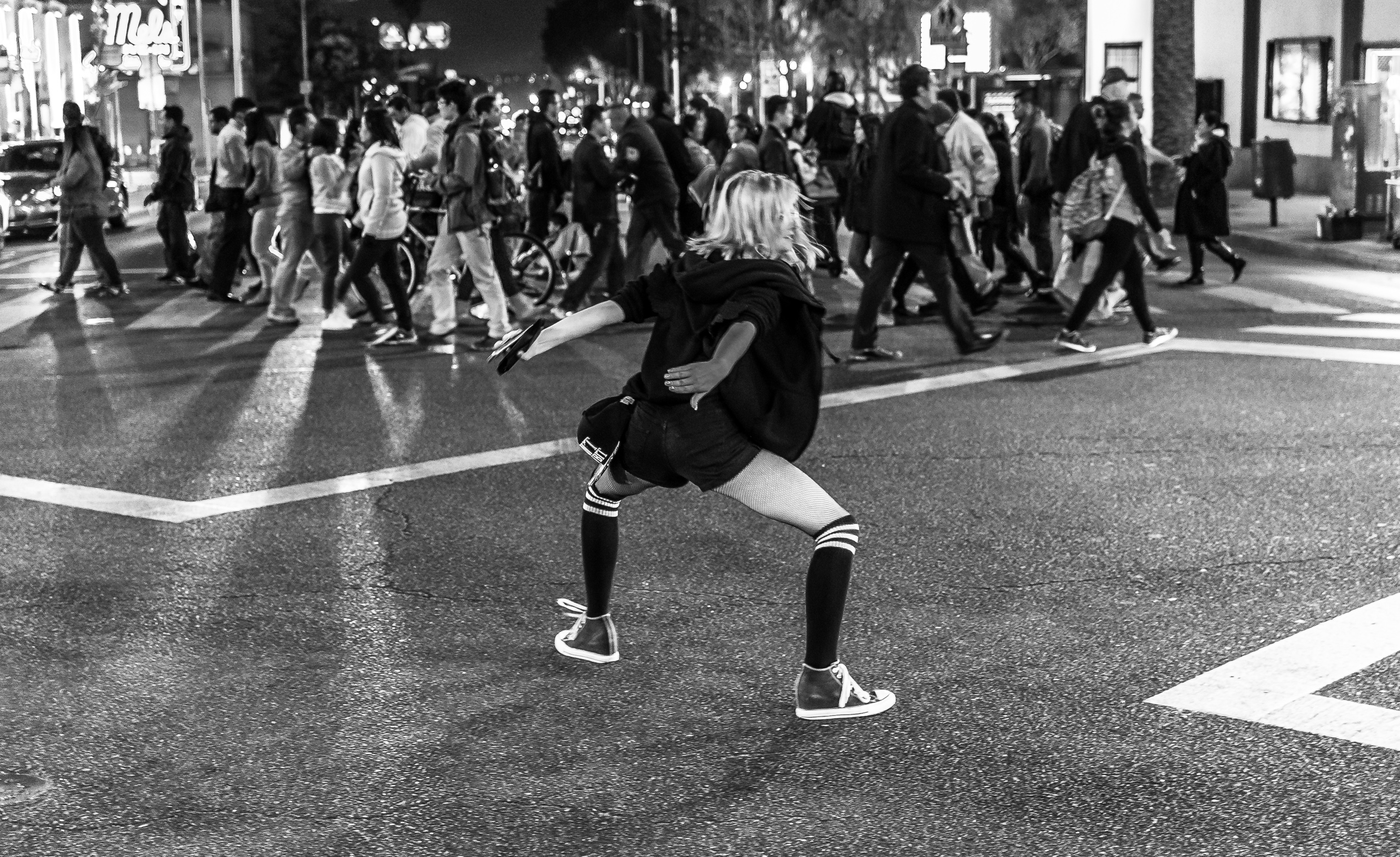 a woman doing a freestyle dance across the four-way crossing at Hollywood Blvd & Highland Blvd in Hollywood, Los Angeles, California