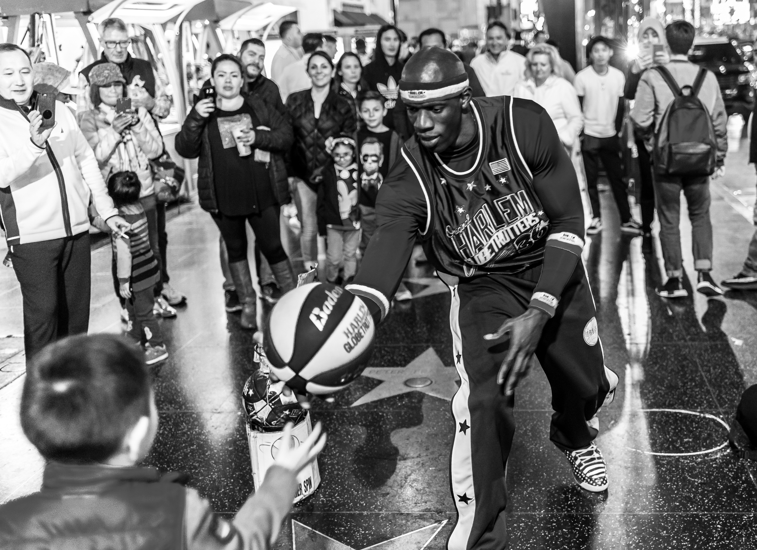 "A ""Harlem Globetrotter"" character on Hollywood Blvd hands a basketball to a young child"