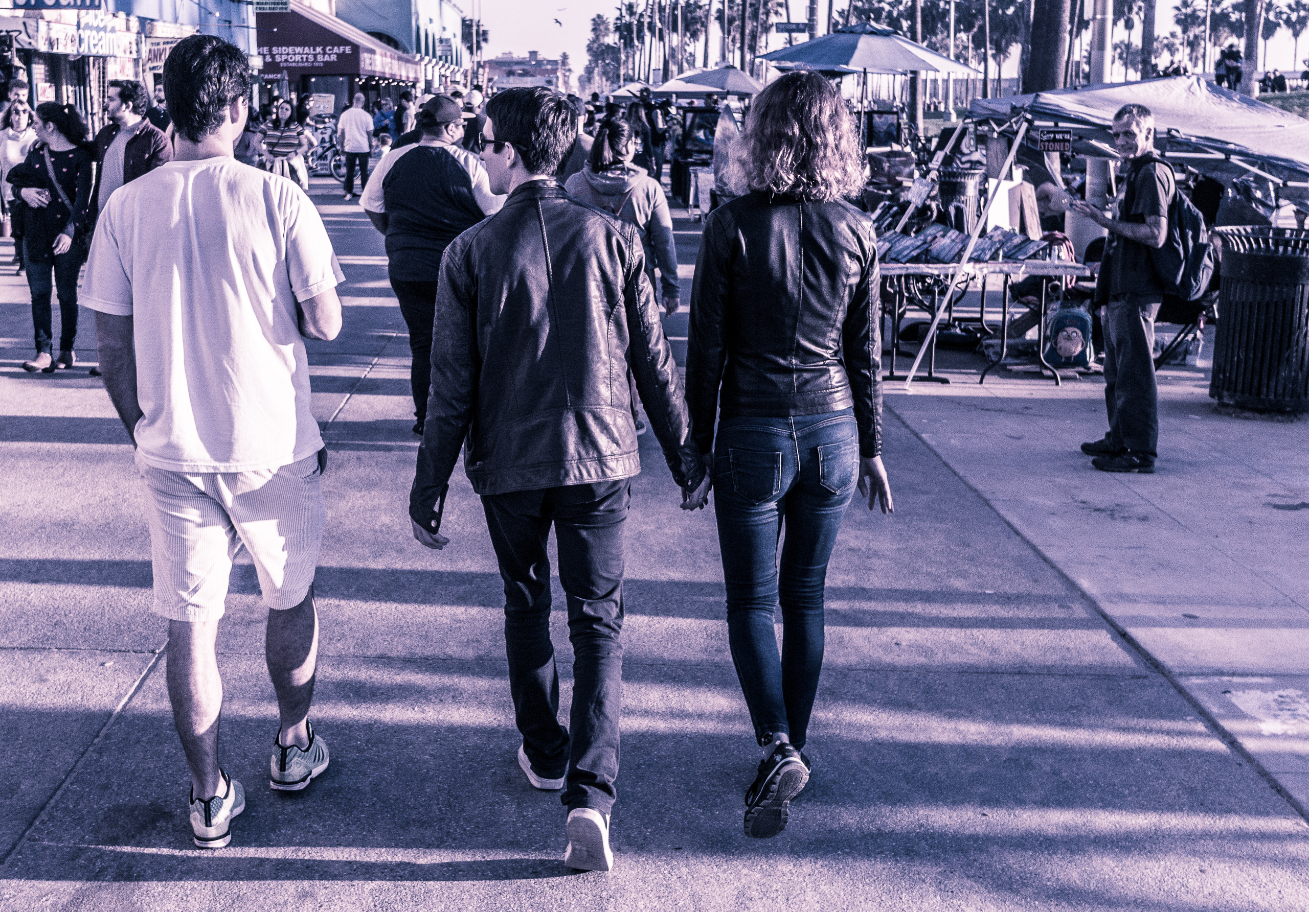 a couple walking on the Venice Boardwalk in Venice Beach, CA. The guy has a loose fitting leather jacket and loose fitting denim pants. The girl has a slim-fitting leather jacket and slim-fitting denim pants