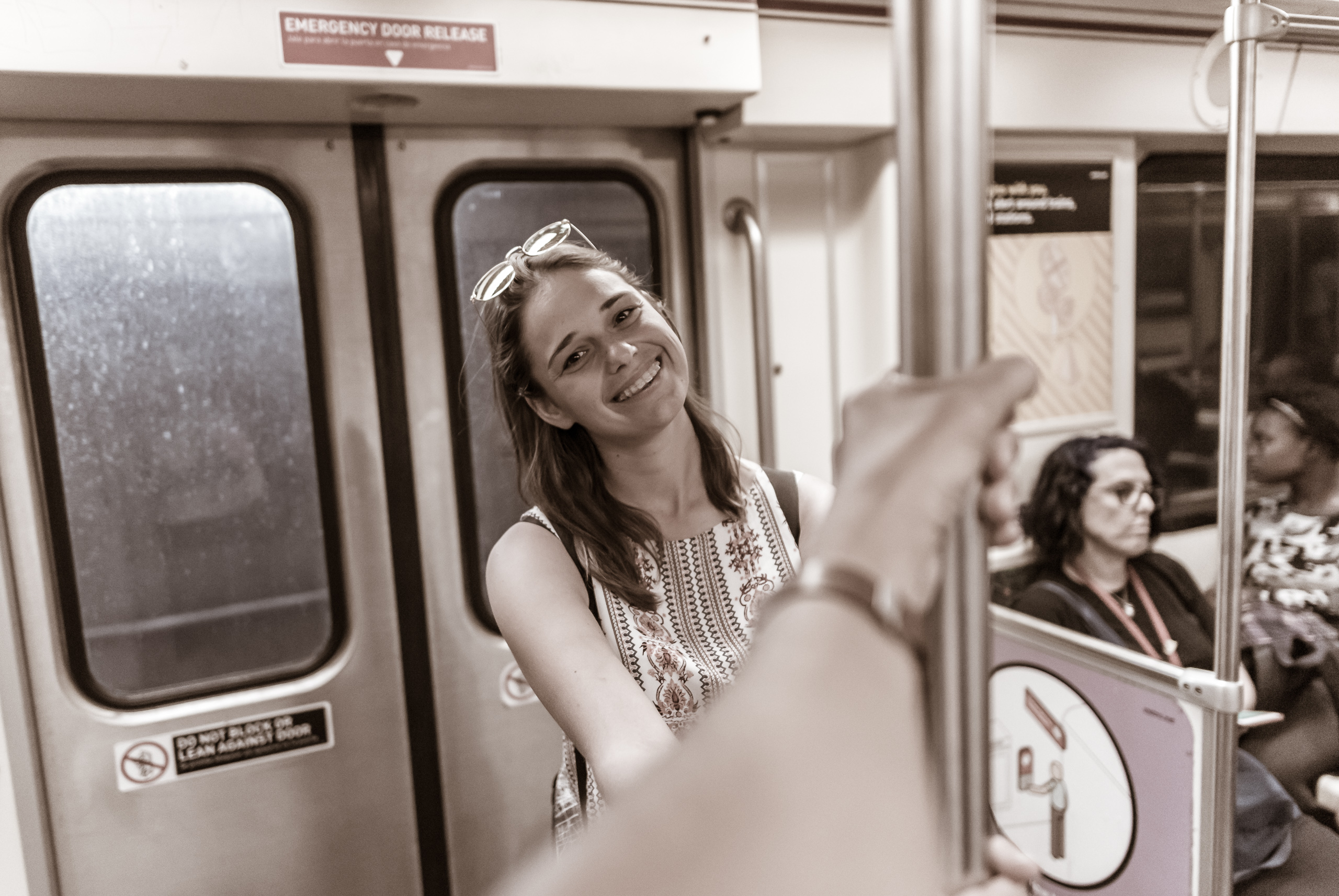 my hand holding a bar in the middle of a Red Line subway car and Kristina smiling from the other side of the bar