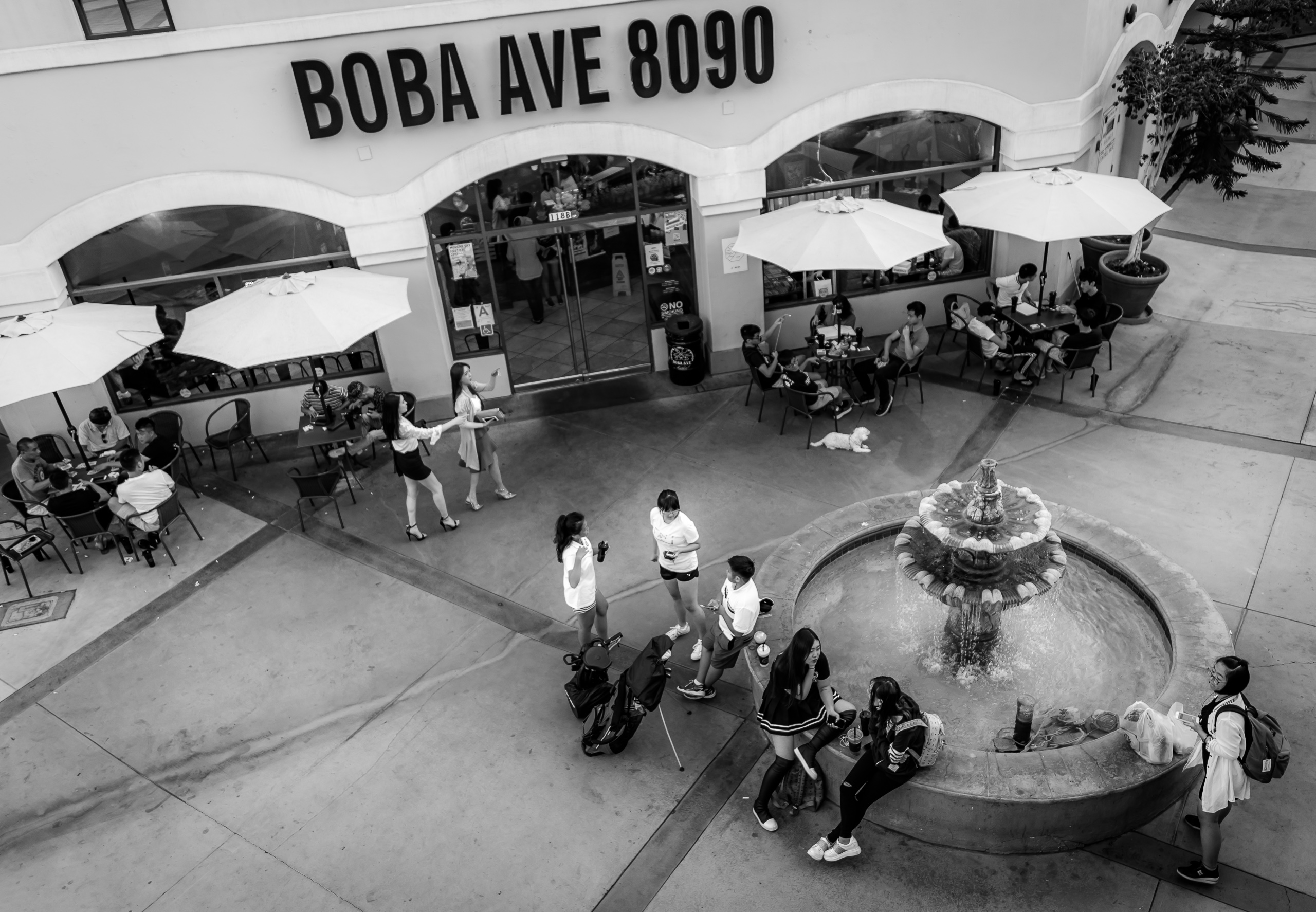 2nd story view looking down on the entrance to Boba Ave and showing the plaza in front with a fountain and people gathered at tables, the fountain, and walking around
