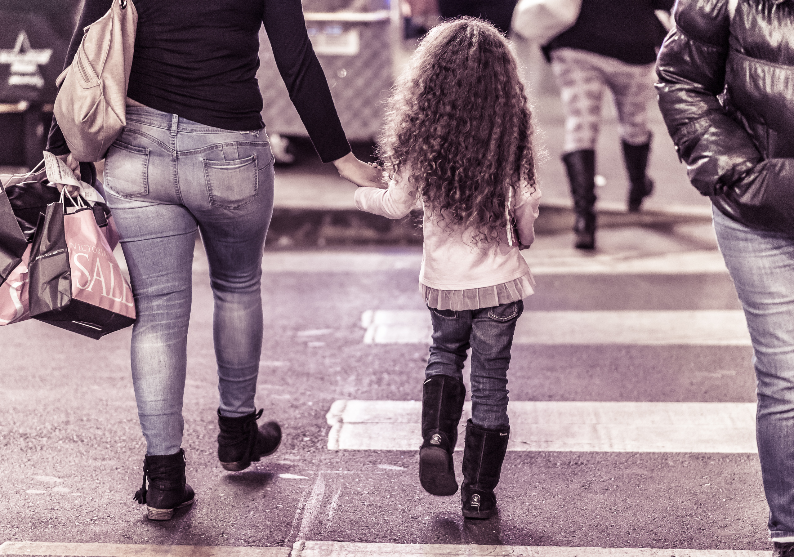 a small girl in uggs crosses the street holding her mother's hand