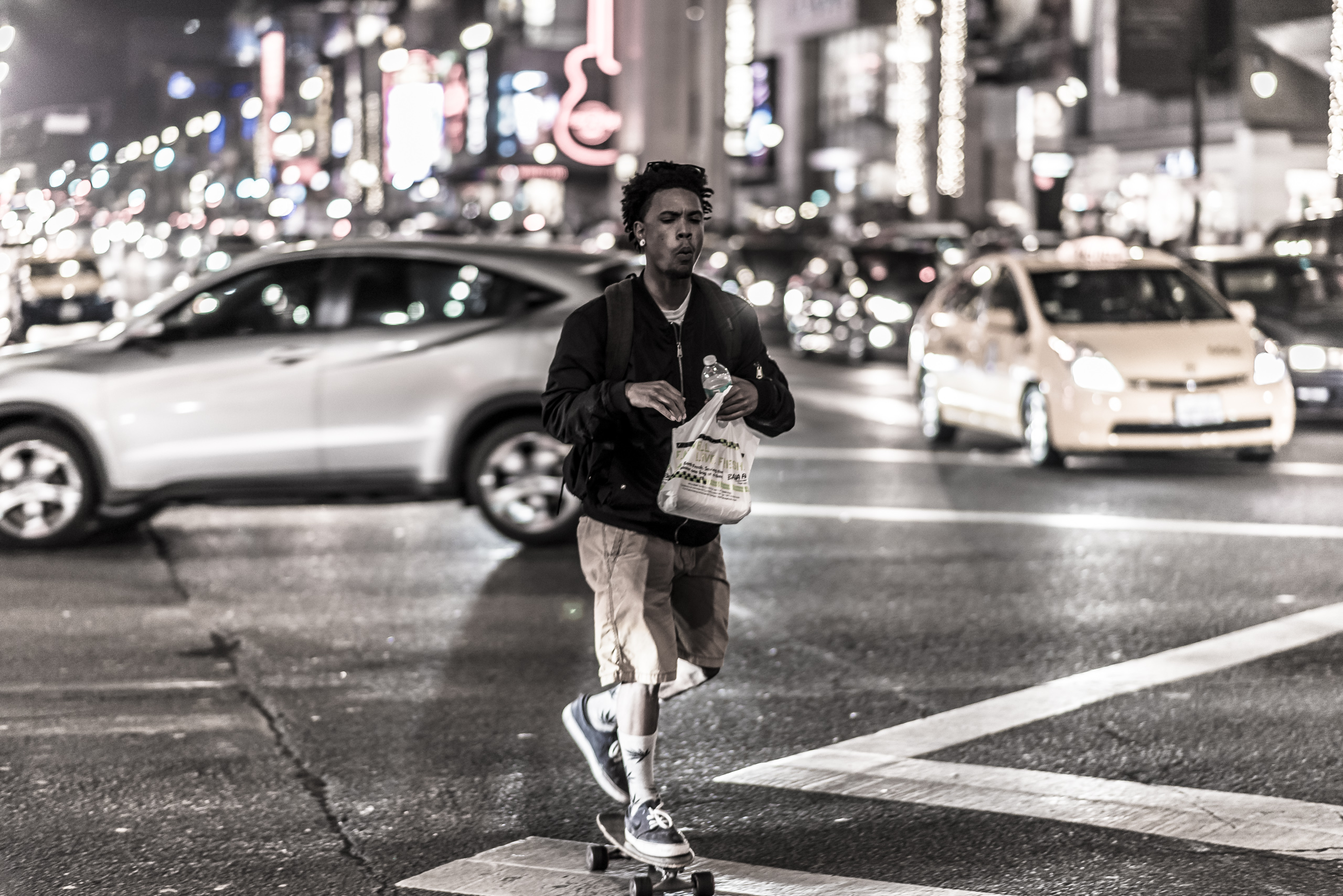A guy on a skate board rides across the intersection of Hollywood and Highland as cars move through the intersection