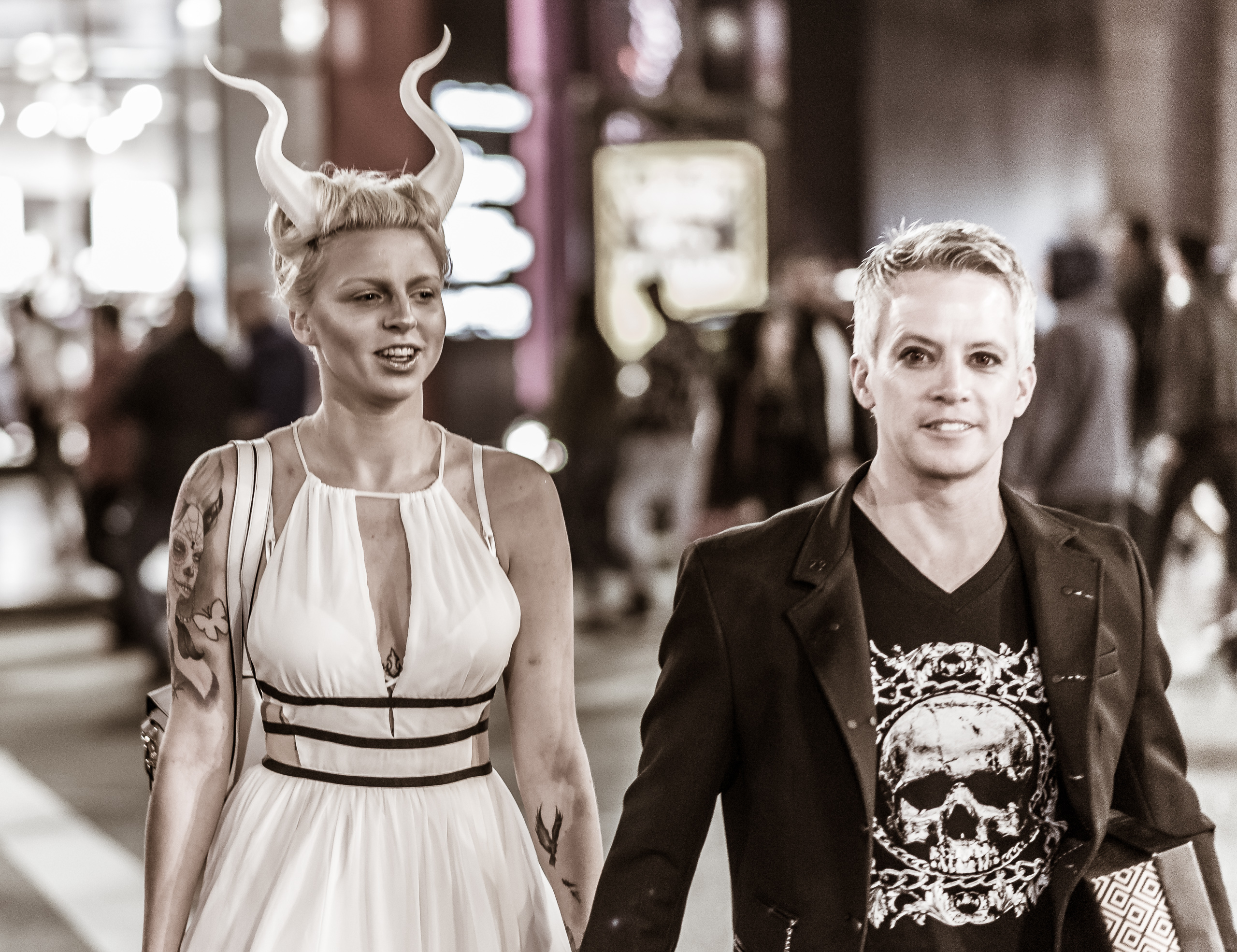 """a woman in a white dress and white """"Maleficent horns"""" walks across the intersection of Hollywood & Highland with a man in black"""