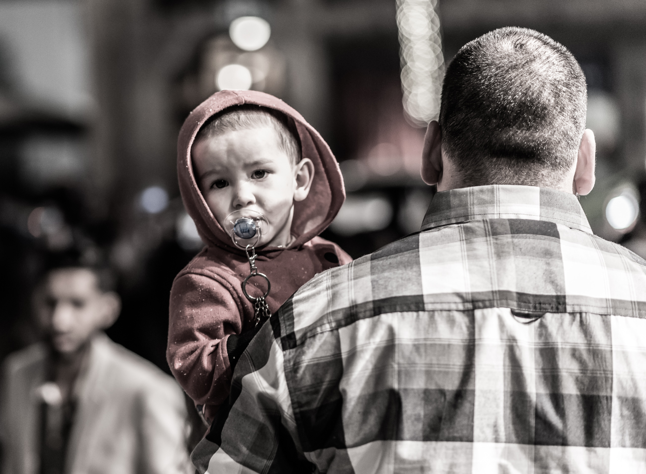 a young boy with a pacifier in his mouth and being carried down the street by his dad