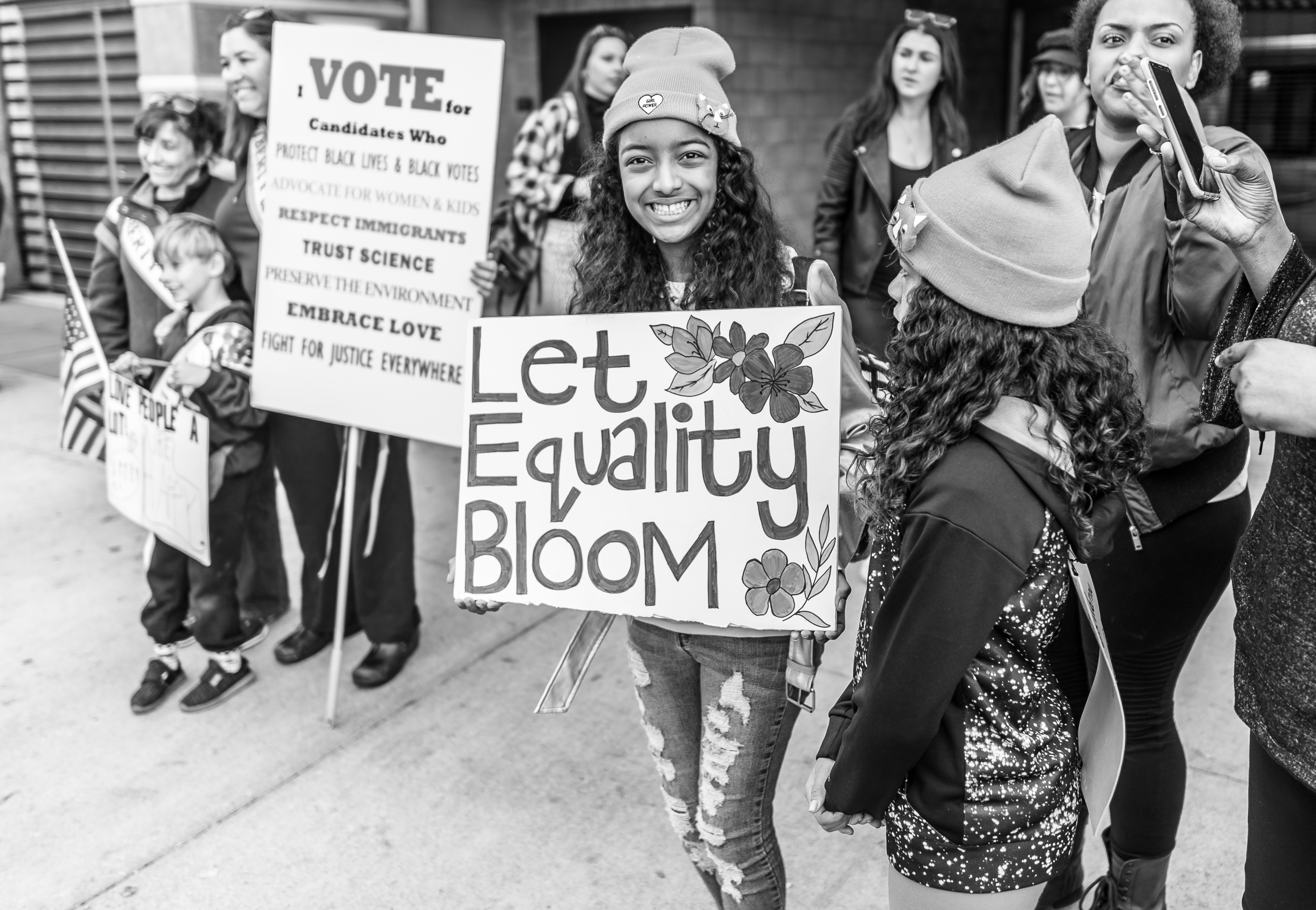 "a young girl holds a sign decorated with painted flowers and the words ""Let equality bloom"" at the 2018 Women's March Los Angeles"