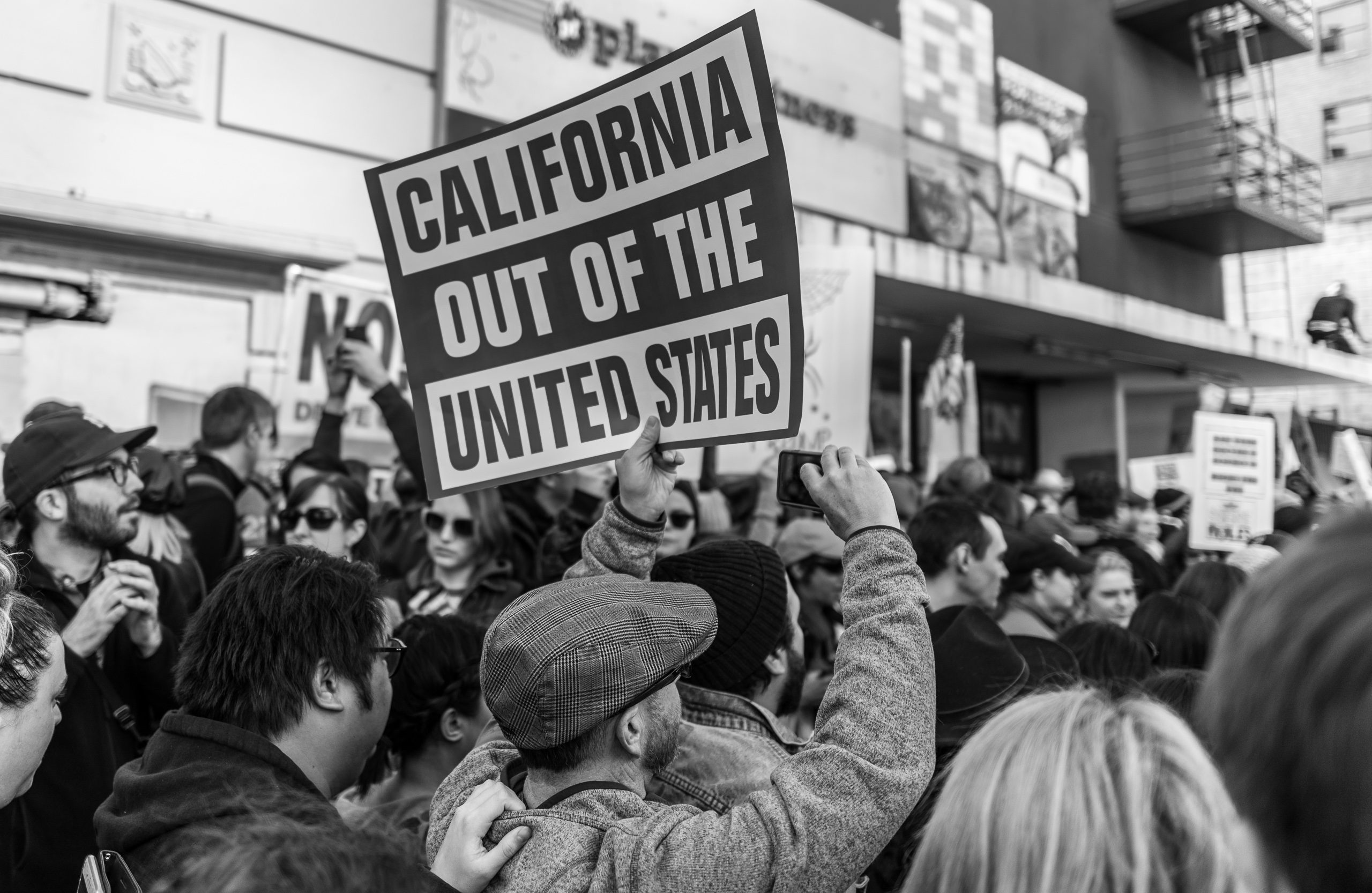 """A man walks in a very dense crowd in the Los Angeles Women's March. He holds a sign in the air that reads """"California out of the United States"""""""