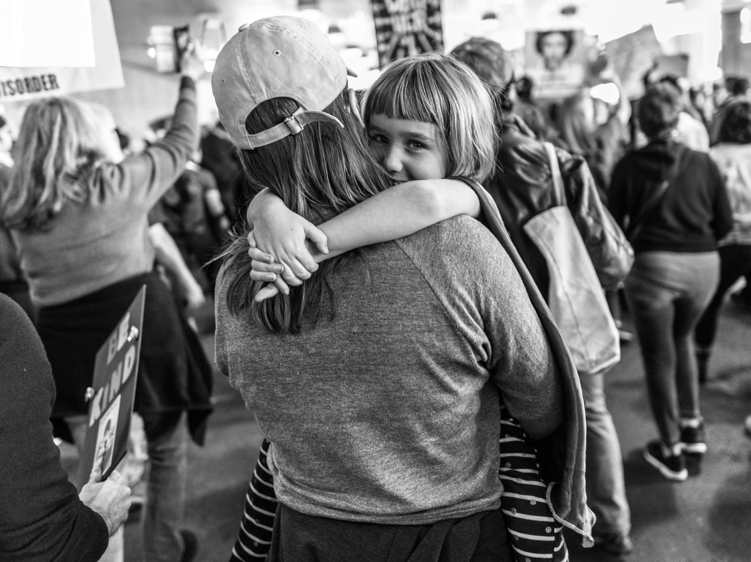 A woman carries her young daughter who hugs mom around the neck and smiles. The daughter wears a super-hero-like cape.