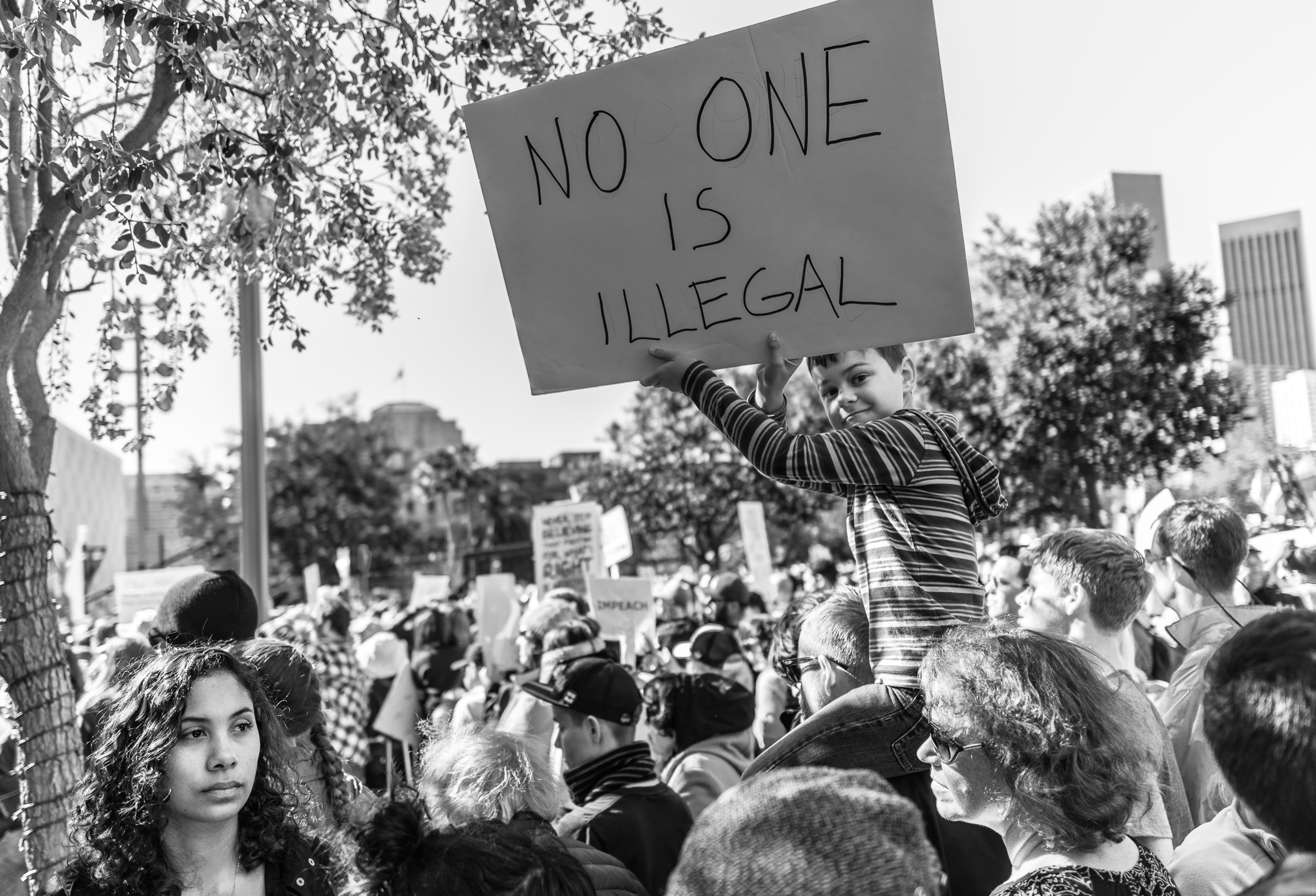 "a young boy sits on his dad's shoulders and holds a sign up in the air that reads, ""no one is illegal"""