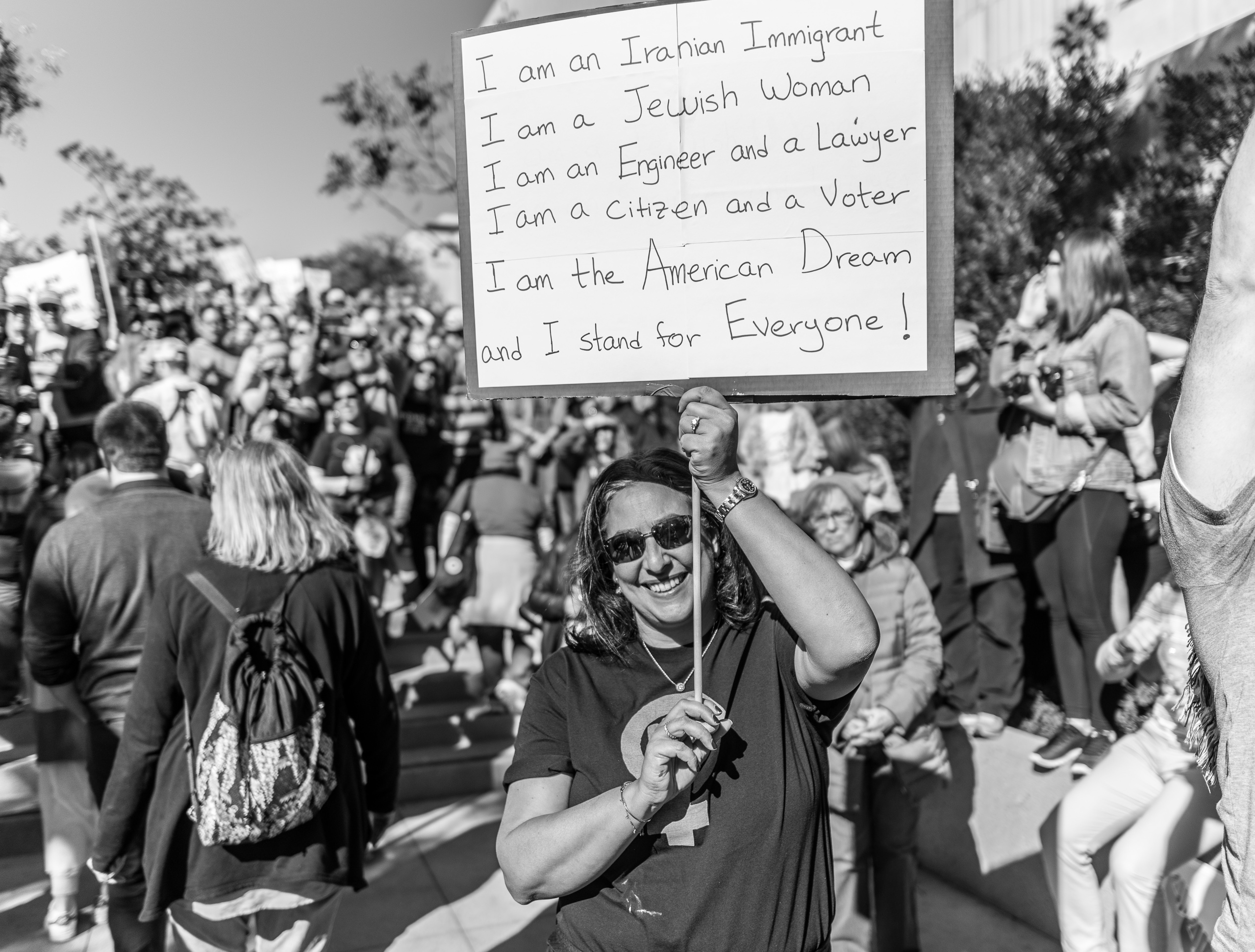 """A woman holds a sign over her head that reads, """"I am an Iranian Immigrant. I am a Jewish Woman. I am an engineer and a lawyer. I am a citizen and a voter. I am the American Dream. And I stand for everyone!"""""""