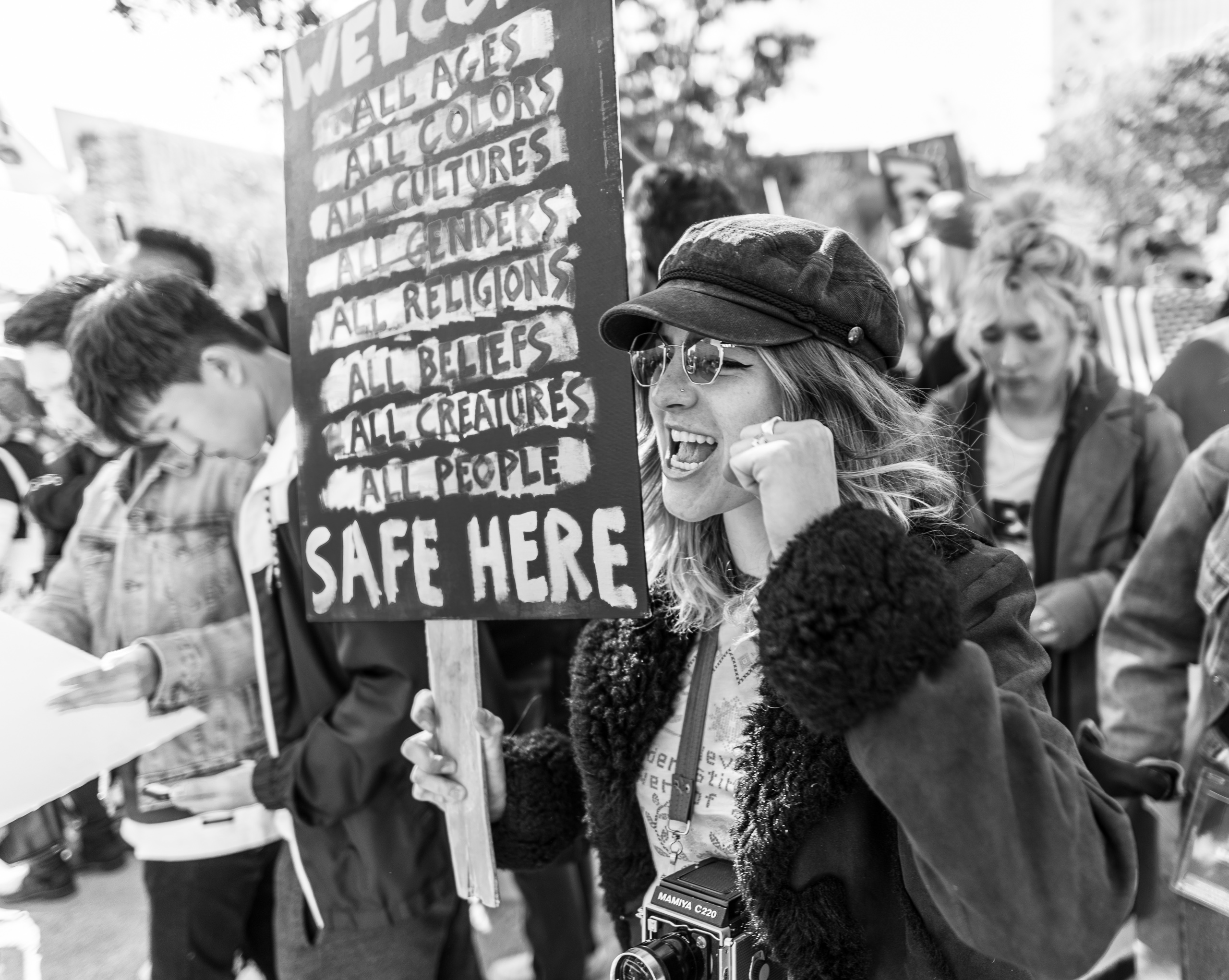 "A woman carries a sign that reads ""safe here"""
