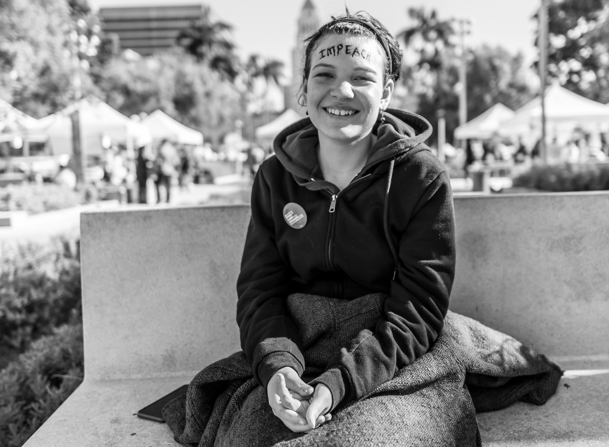 "A woman sits on a bench in the Los Angeles Civic Center. Across her forehead is written the word ""Impeach"". Behind her , in the distance, is Los Angeles' City Hall."
