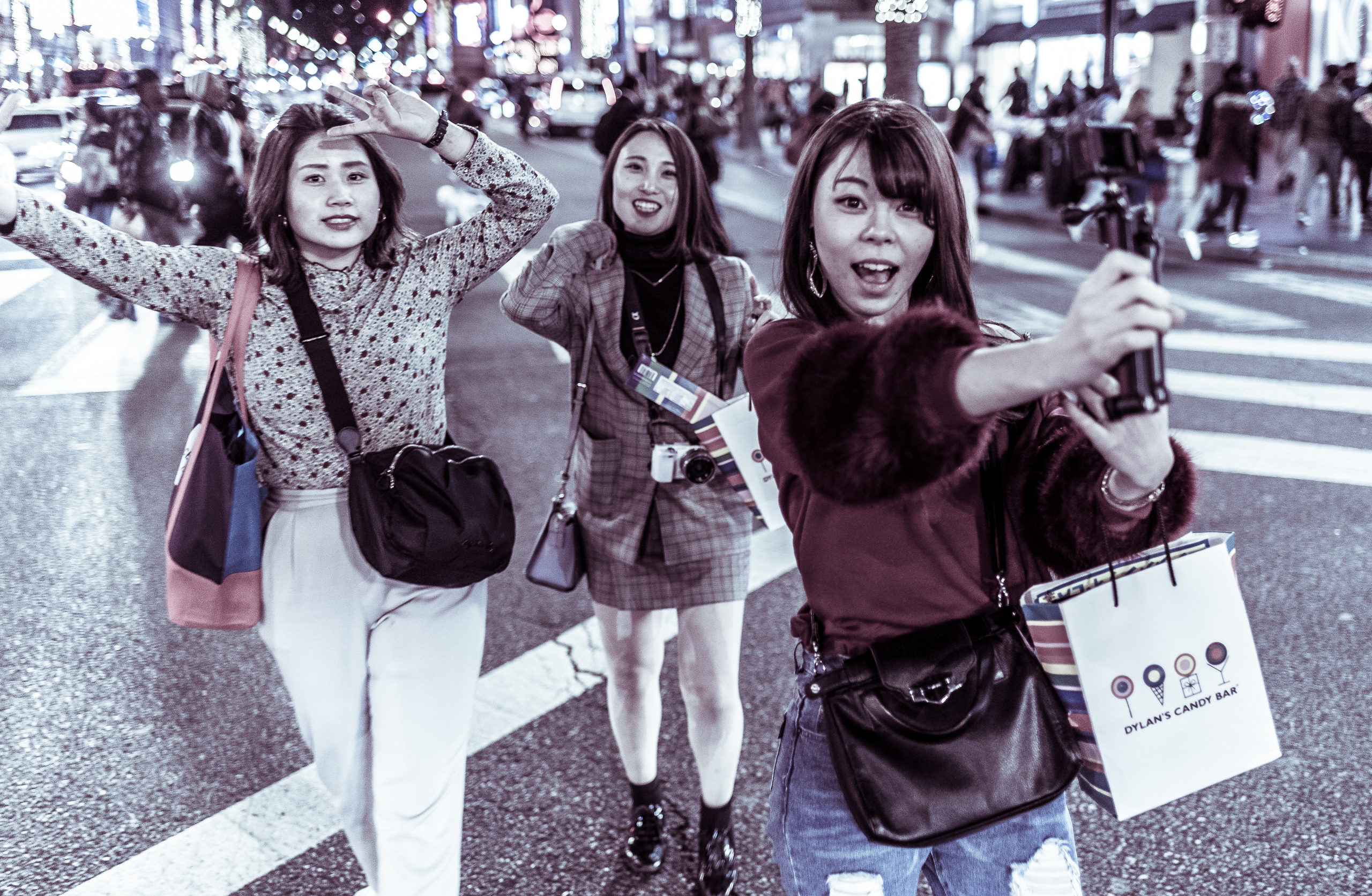 three women take selfies as they diagonally cross through the 4-way crossing at Hollywood & Highland in Hollywood, CA