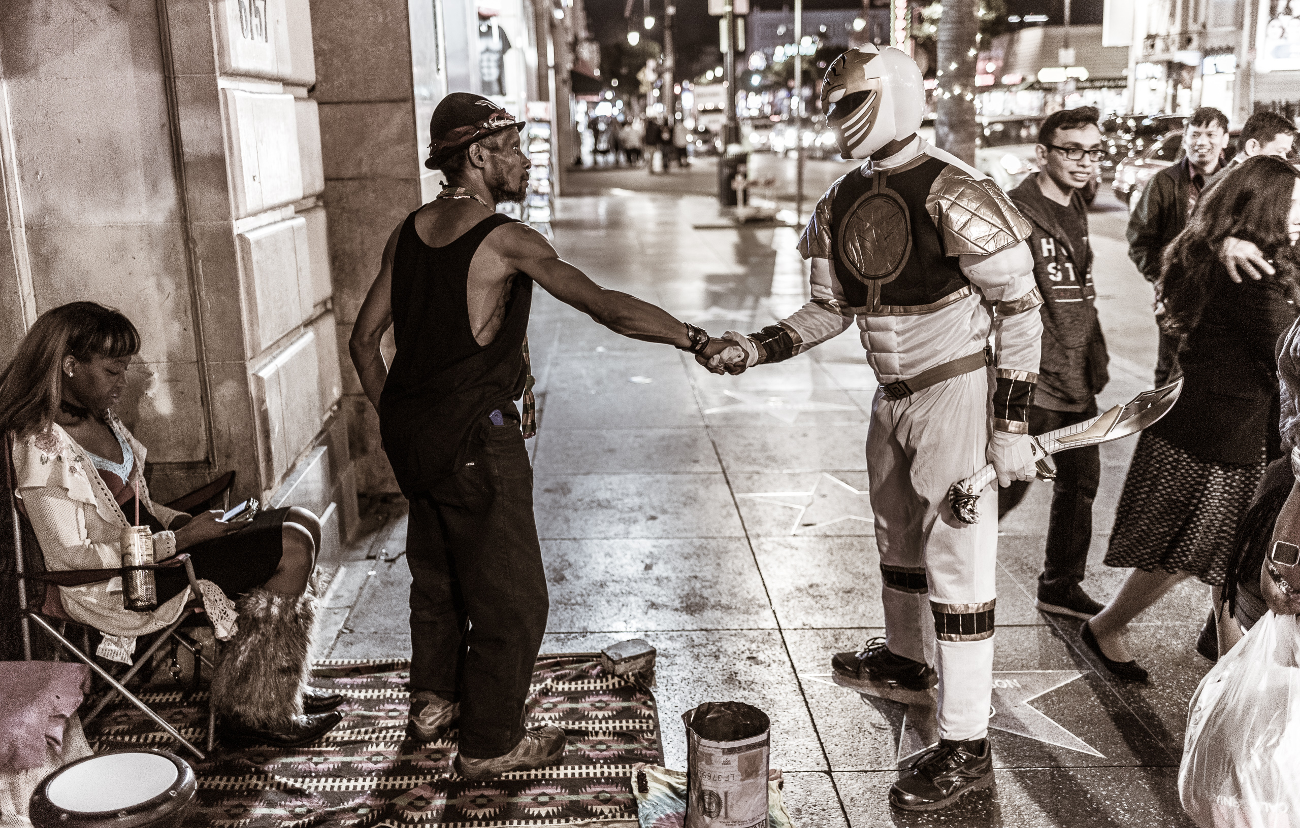 A man on Hollywood Blvd shakes hands with the White Power Ranger.