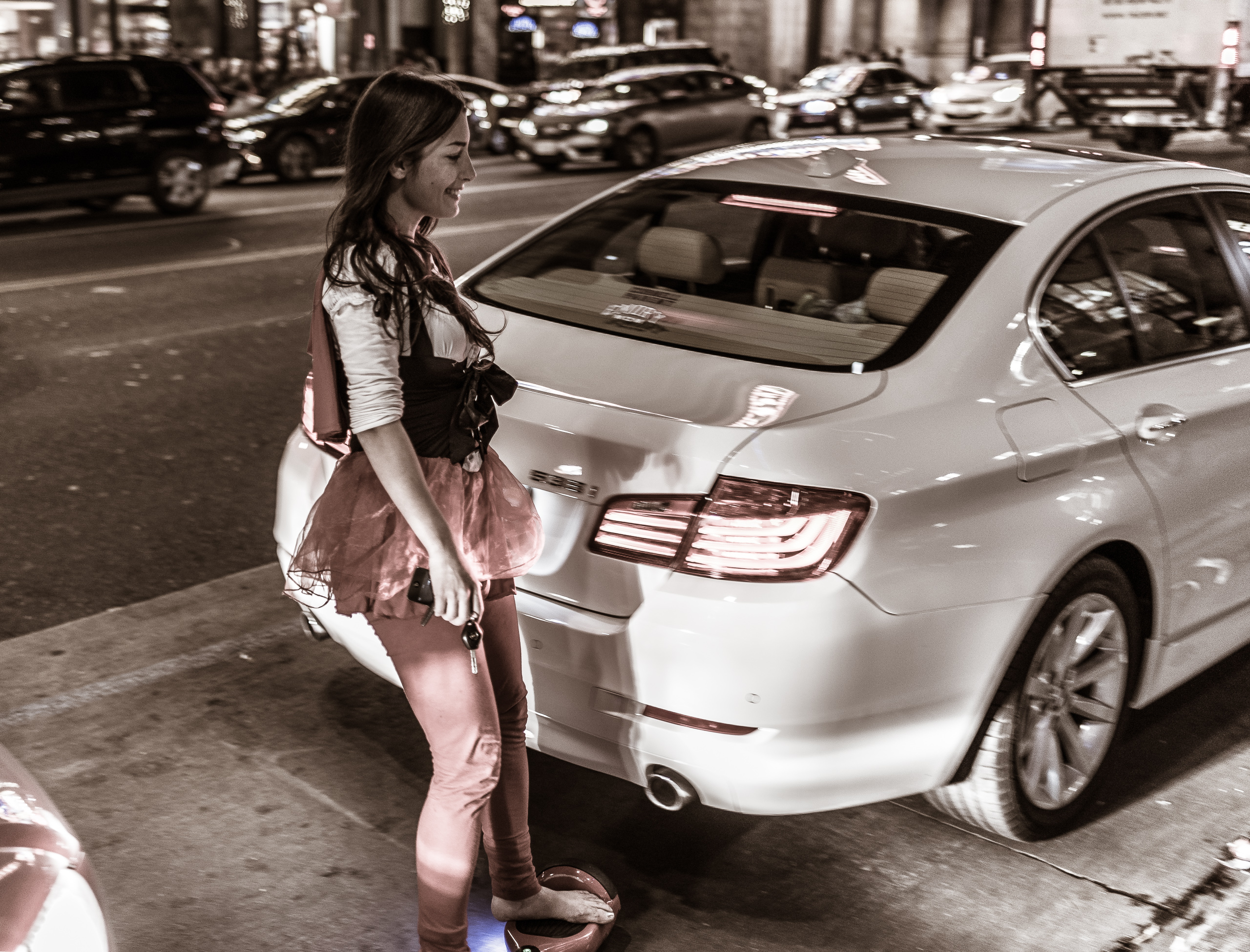 a woman on a hoverboard moves between cars on Hollywood Blvd in Los Angeles, California