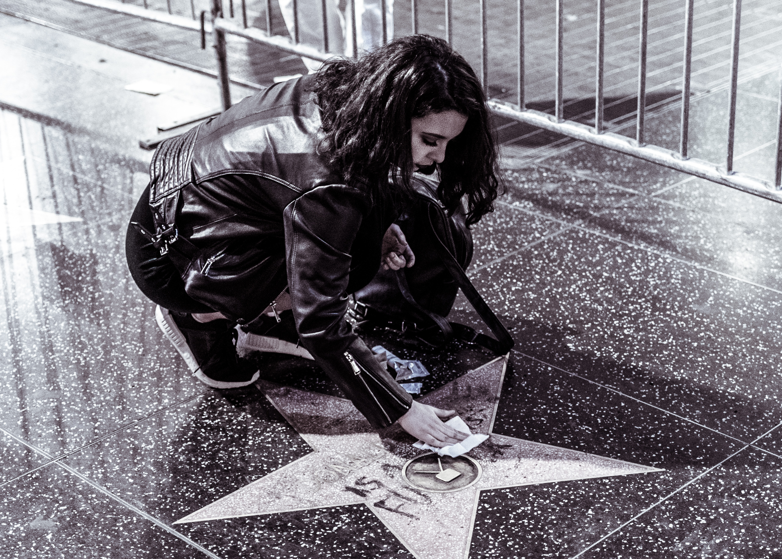 a woman leans over Donald Trump's Star on Hollywood Blvd and cleans mascara off the star