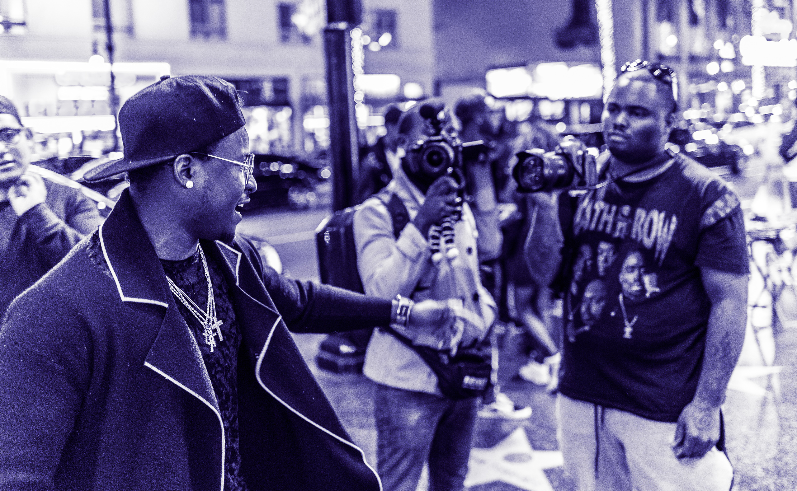 a man wearing gold chains oozes charisma toward two video cameras on Hollywood Blvd.