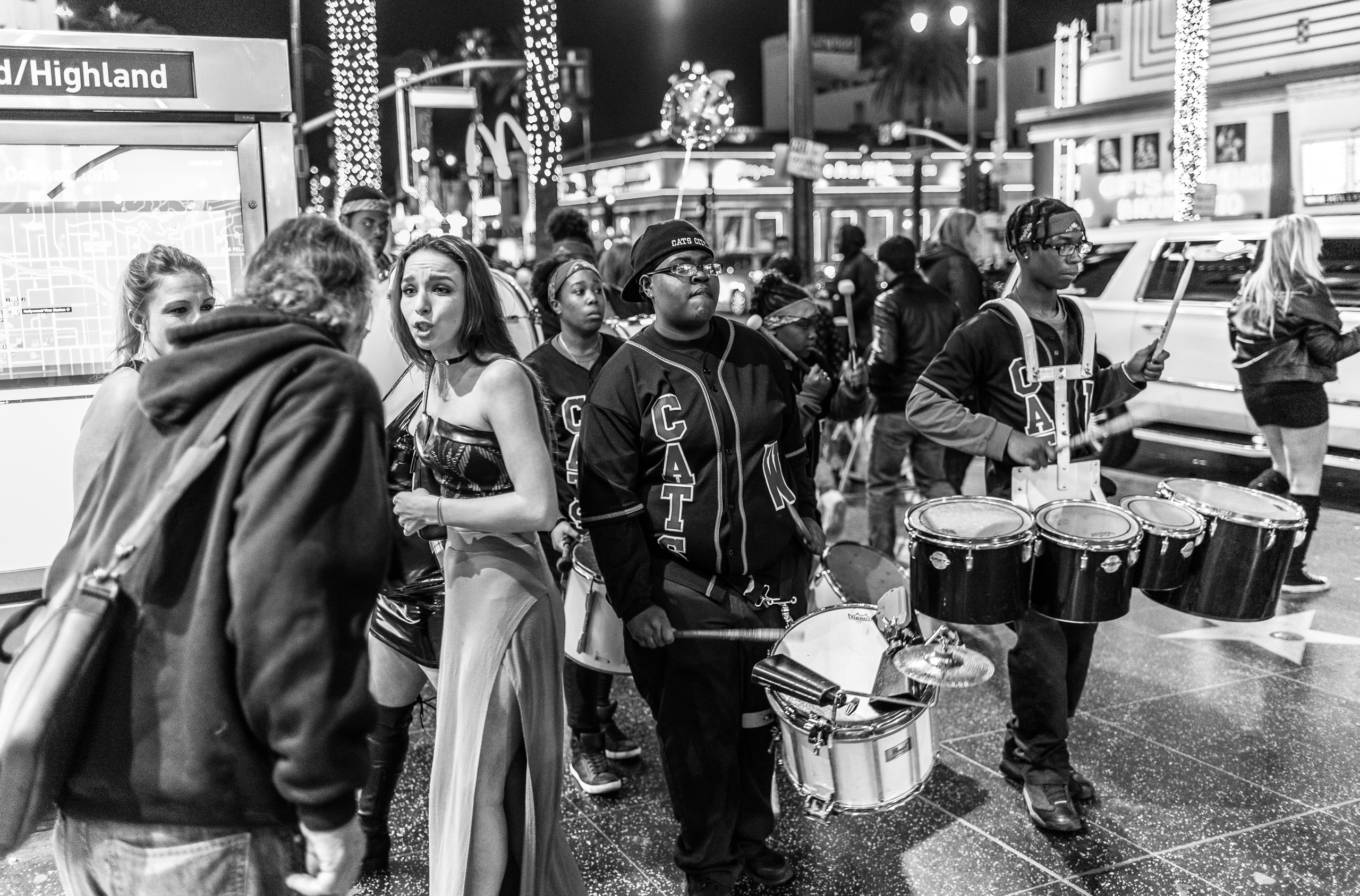 a high school band marching through pedestrians on the sidewalk at Hollywood Blvd.