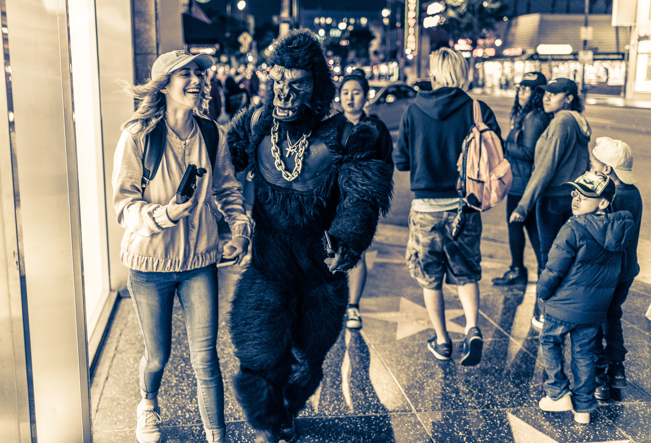 a girl and a gorilla walk down the sidewalk on Hollywood Blvd.