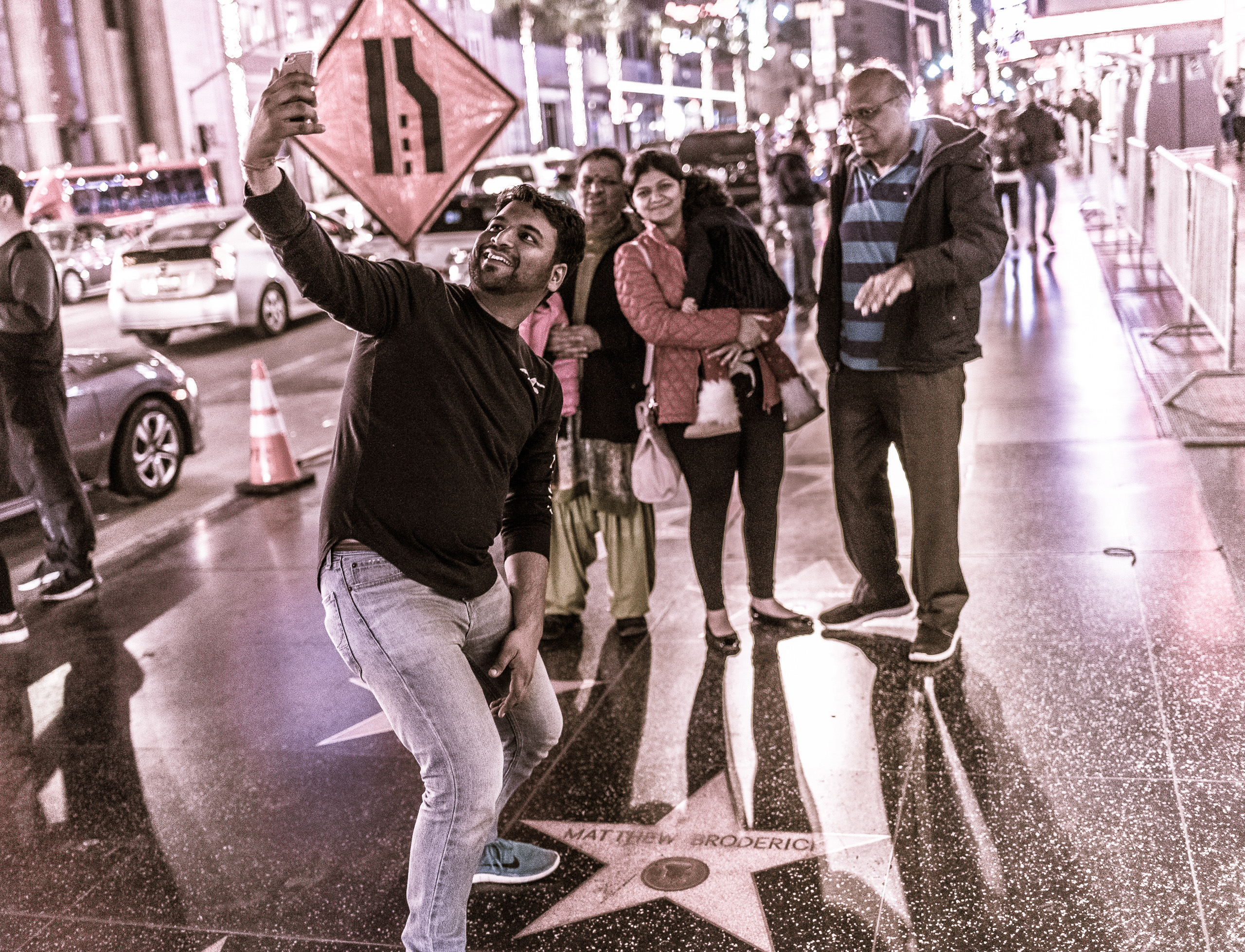 a man stands over Matthew Broderick's star on Hollywood Blvd, holds his phone high in the air above him, and takes a selfie with the star