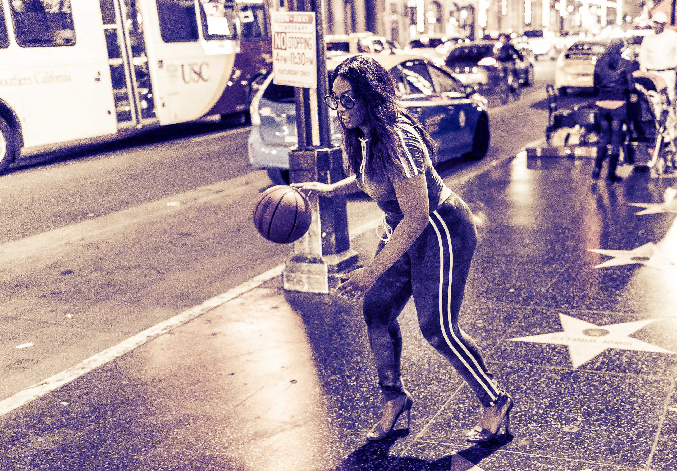 a woman in high heels dribbles a basketball on Hollywood Blvd.