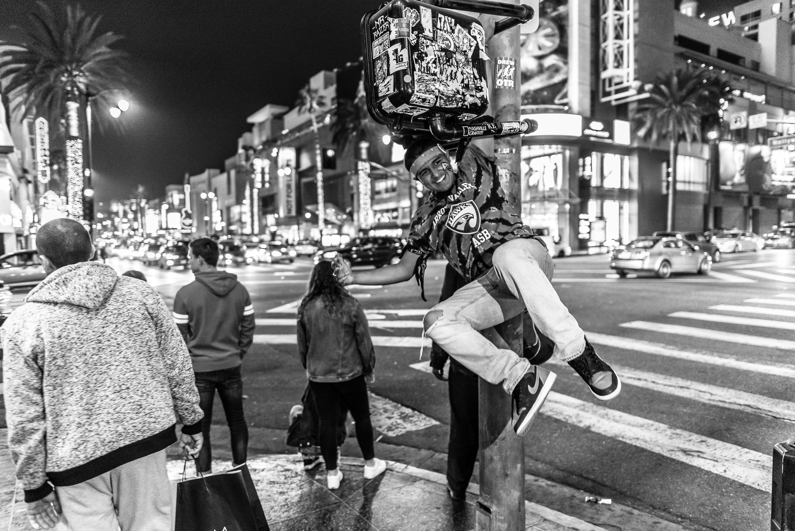 a young man hangs from a streetlight on the corner of Hollywood and Highland in Hollywood, Los Angeles, California