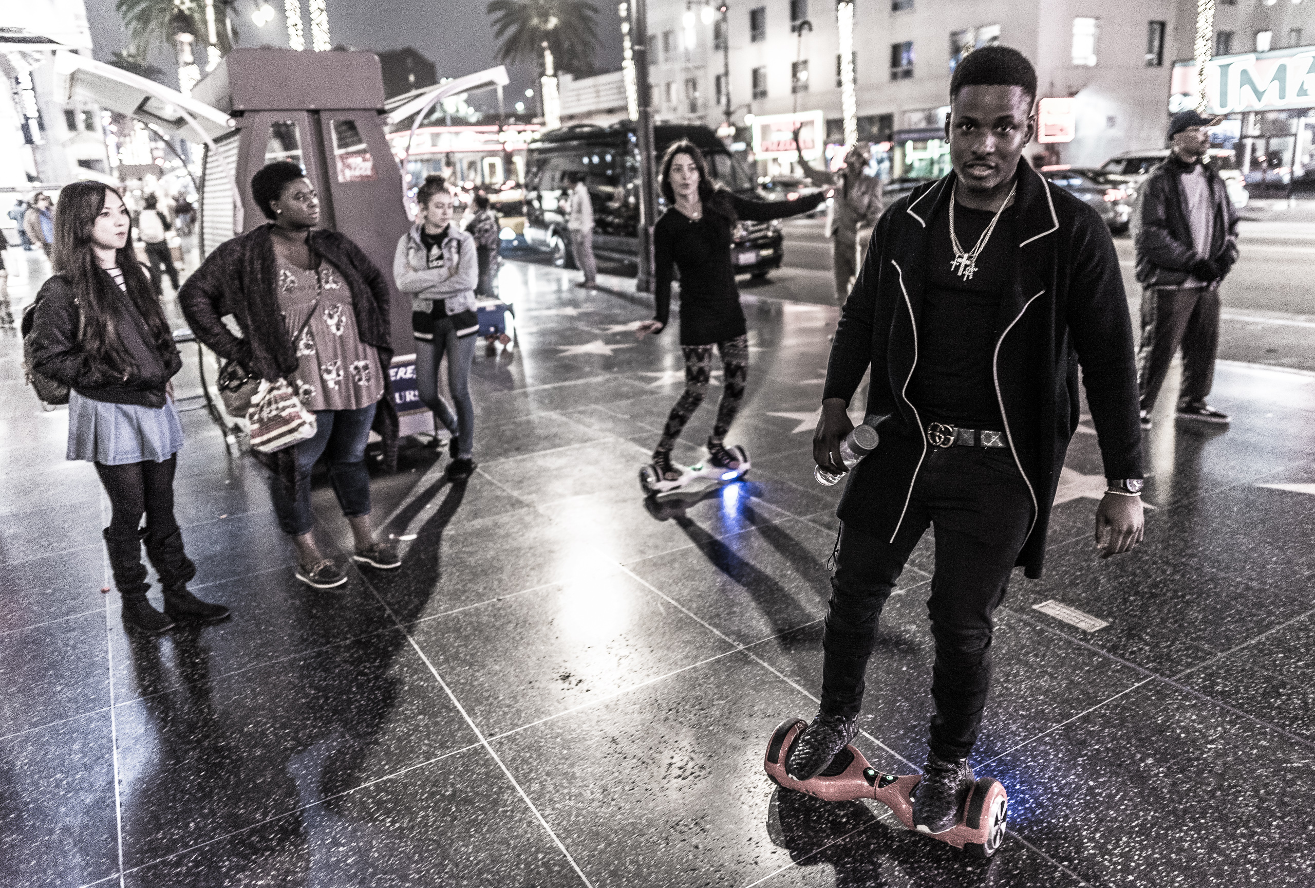 two people ride hoverboards in circles on the wide sidewalk in front of the Hollywood & Highland shopping center in Hollywood, Los Angeles, California