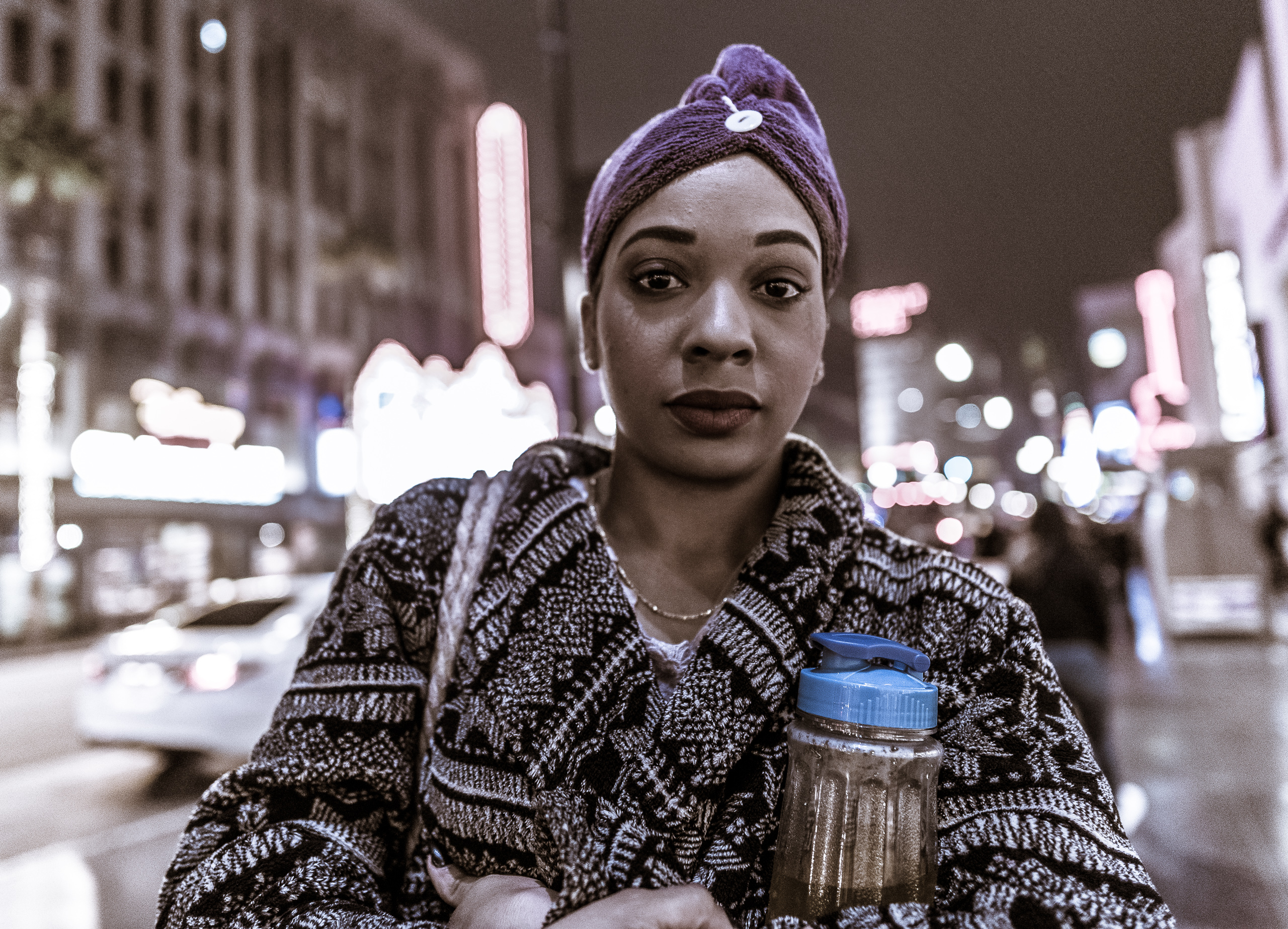 a woman in a purple head scarf looks gently at the camera while standing on the sidewalk at Hollywood Blvd.