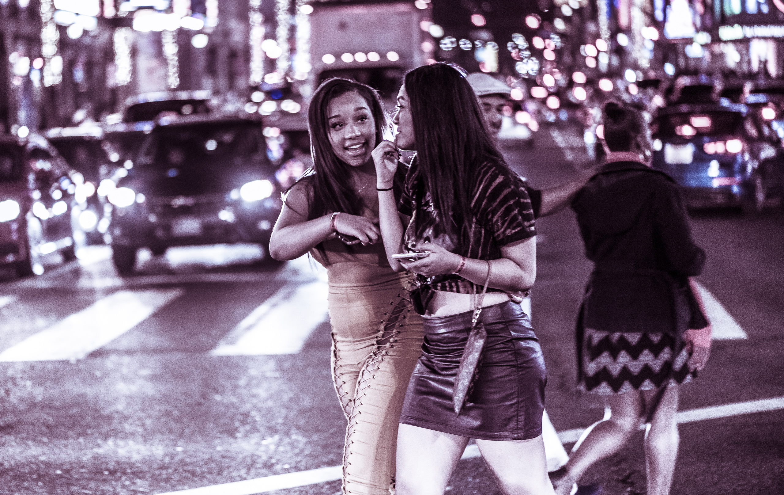 a woman in a lace-up catsuit and  a woman in a leather miniskirt walk across the street together
