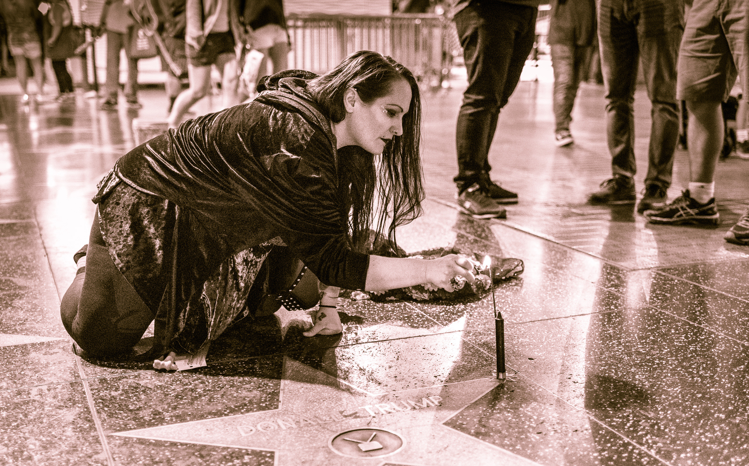 Erin Leigh in a flowing robe kneels at Donald Trump's Star on Hollywood Blvd and lights a candle on one of the points of the star