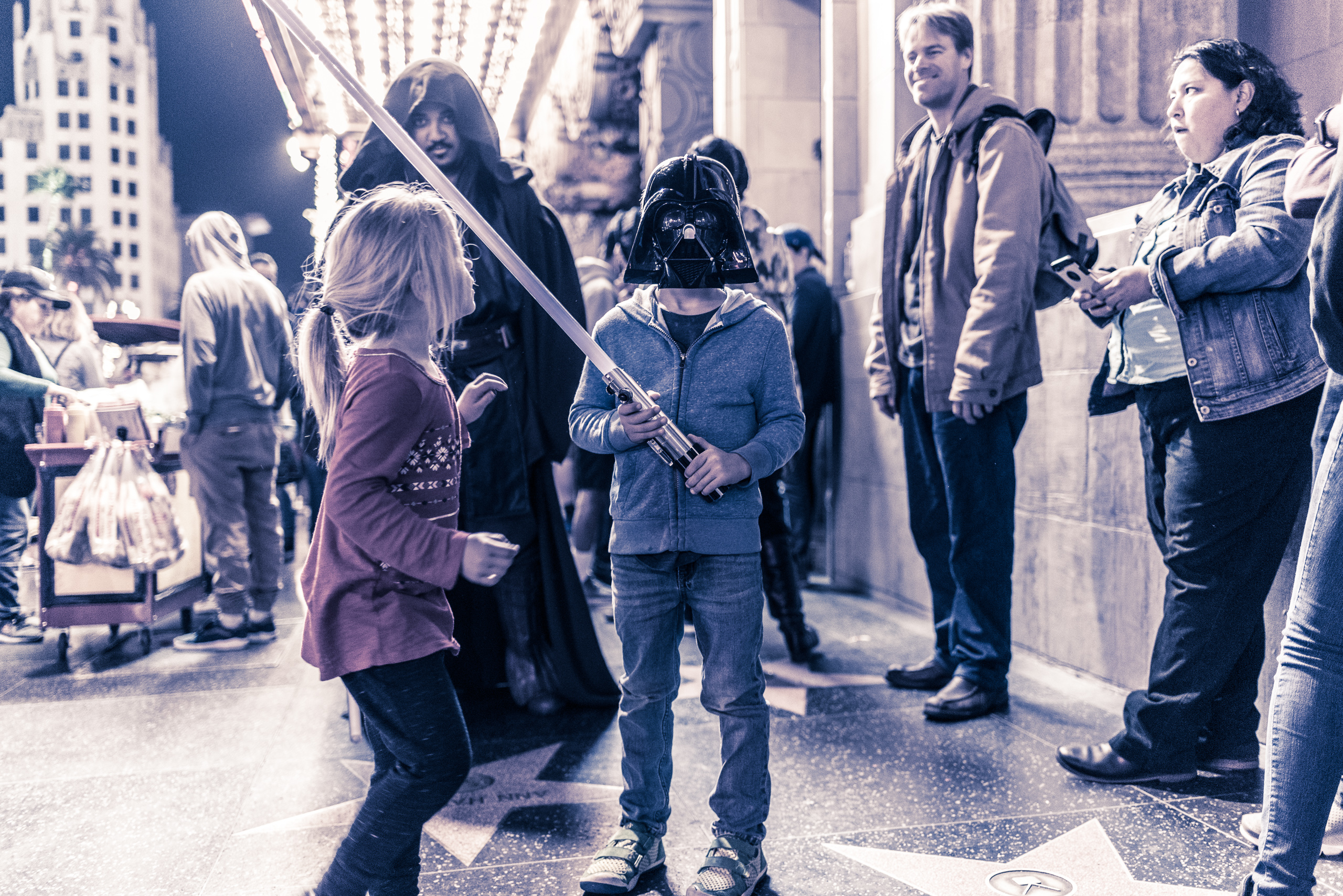 a young boy in a Darth Vader mask holds a light saber in front of the El Capitan theater on Hollywood Blvd.