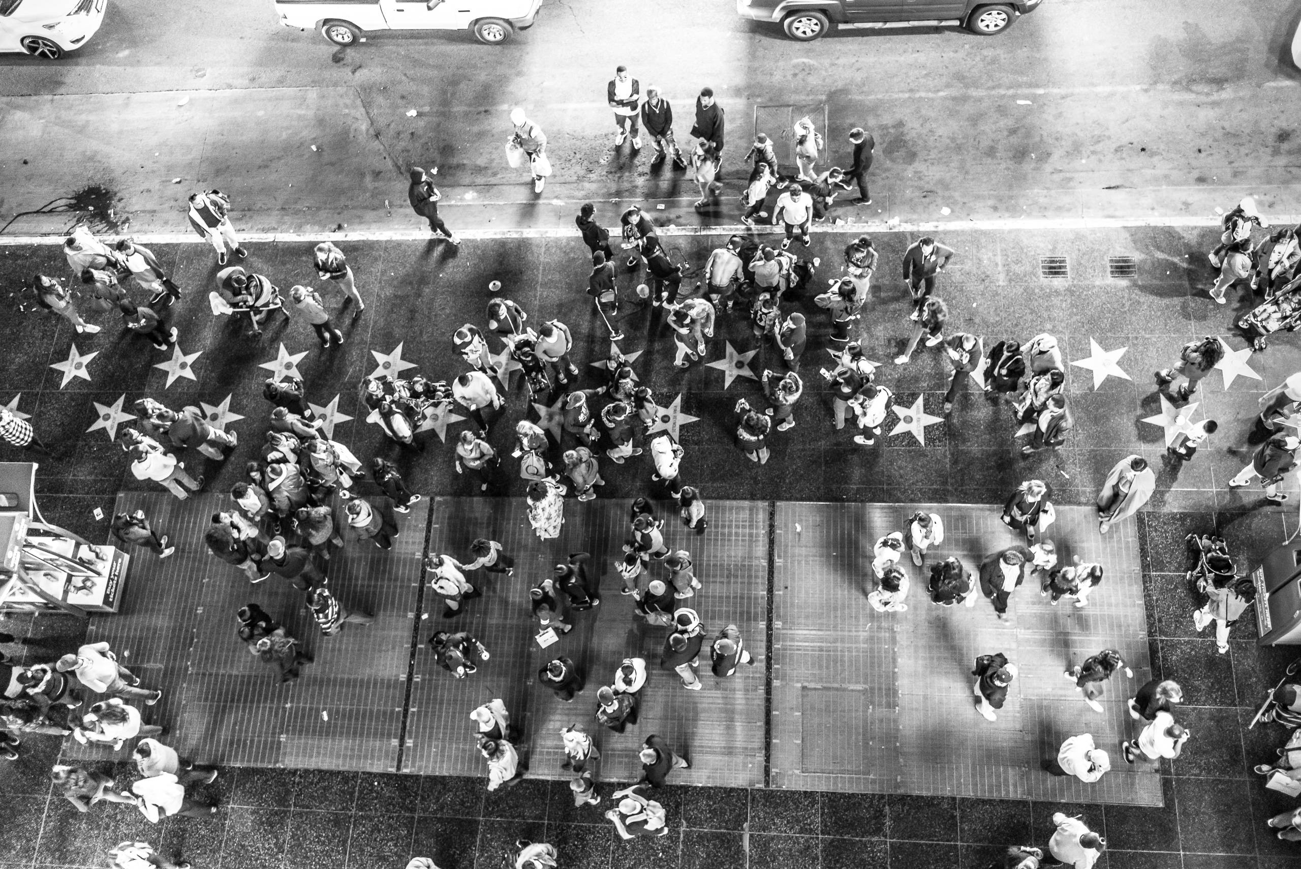 shot looking down on the sidewalk and street at the Hollywood & Highland center / Dolby Theatre on Hollywood Blvd. Many dozens of people are scattered on the sidewalk and street and interspersed between them are stars  on the Hollywood Walk of Fame