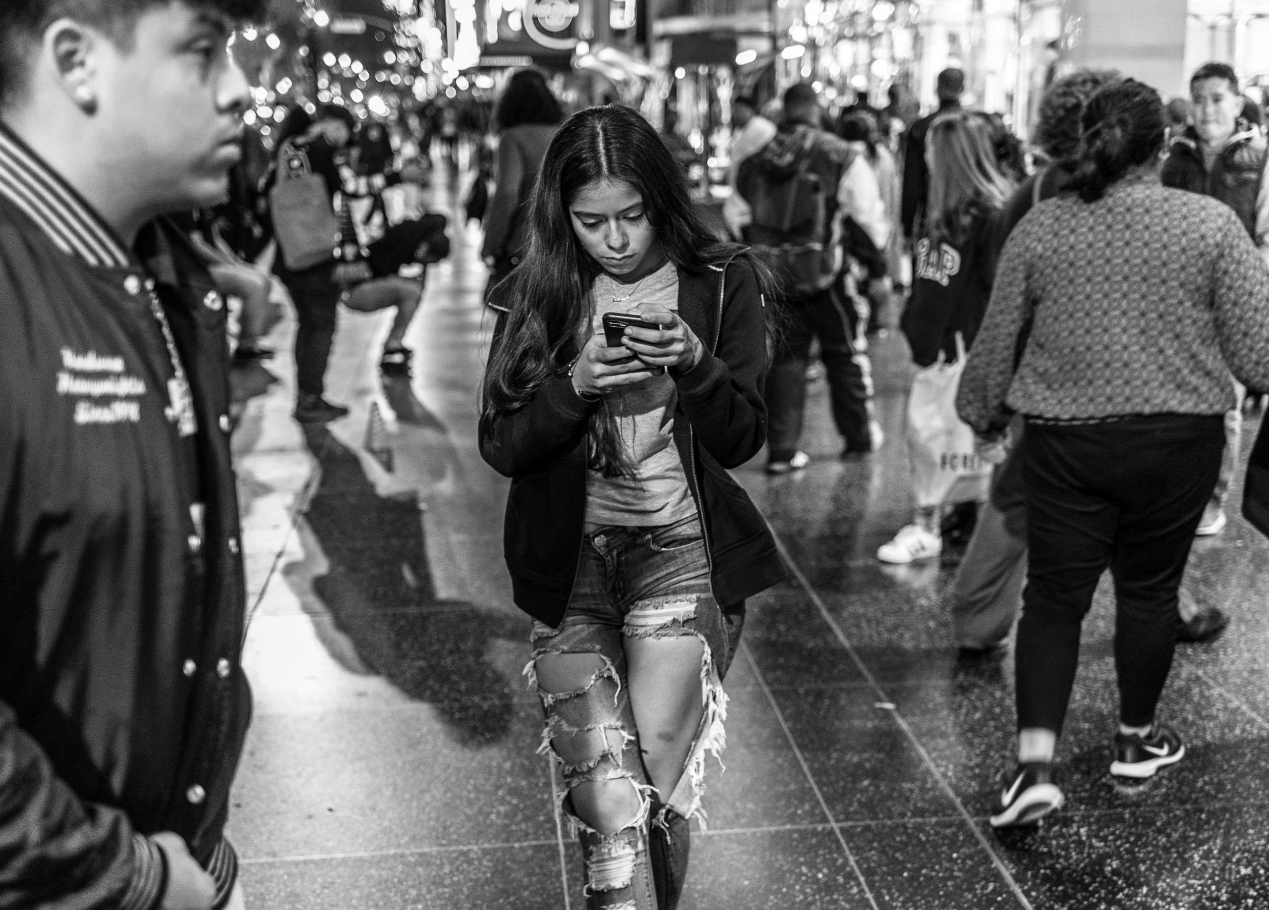 a young girl with torn jeans and a cell phone held before her face in both hands, walks down Hollywood Blvd.