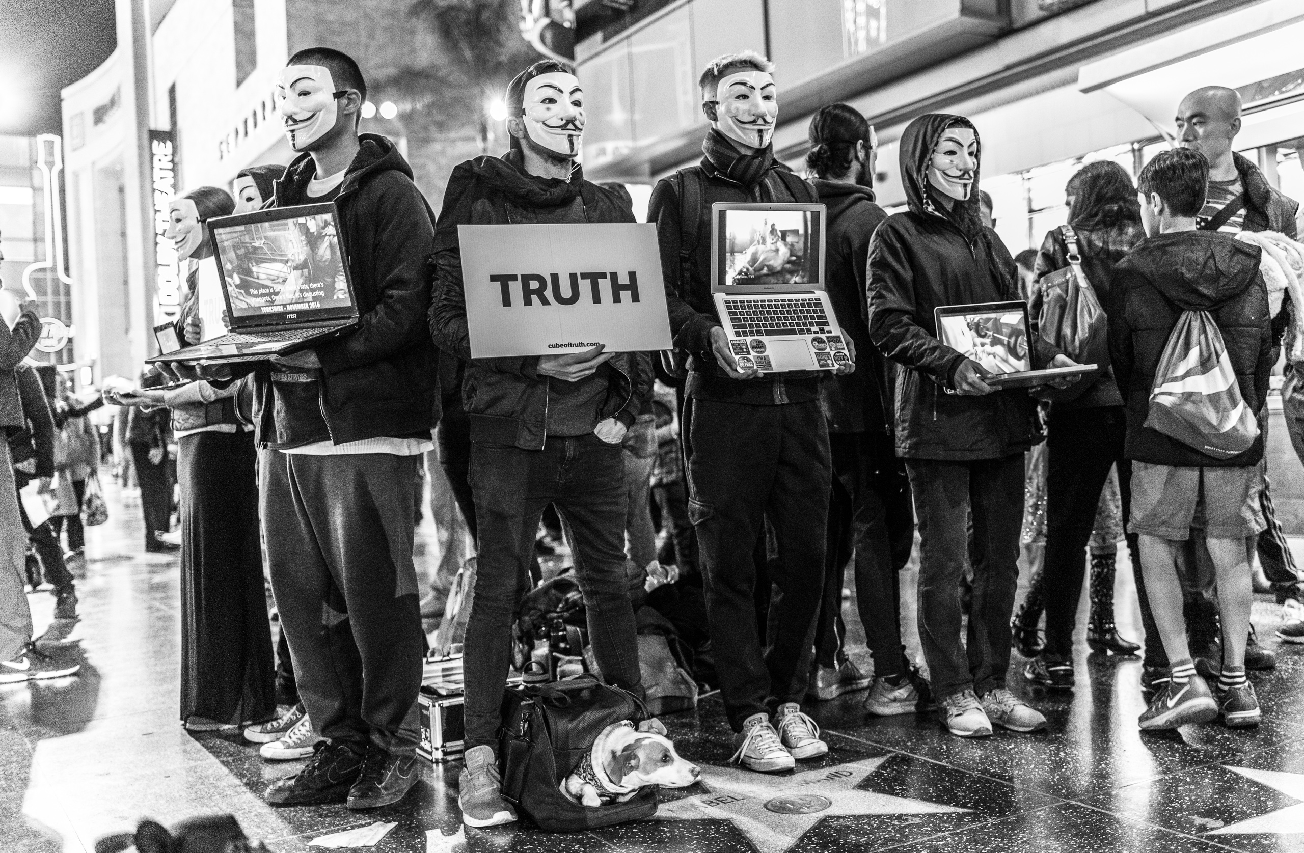 """PETA members at Hollywood & Highland holding laptops showing animal cruelty videos and wearing """"anonymous"""" or """"V for Vendetta"""" masks"""