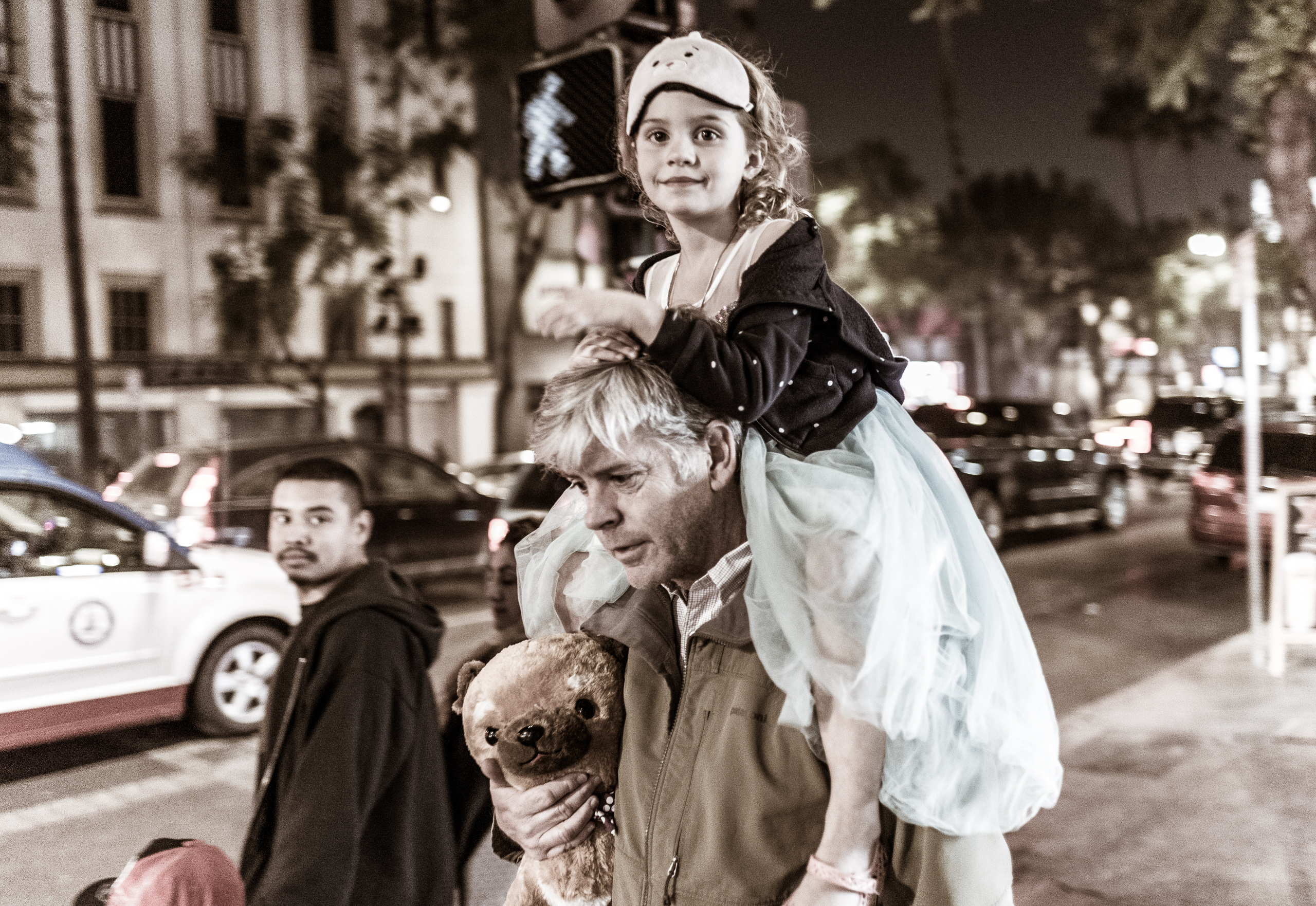 a young girl with a cat mask on her forehead rides on her dad's shoulders